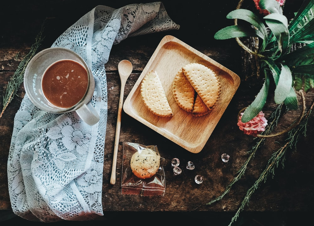 flat-lay photography of pastry on tray beside glass mug