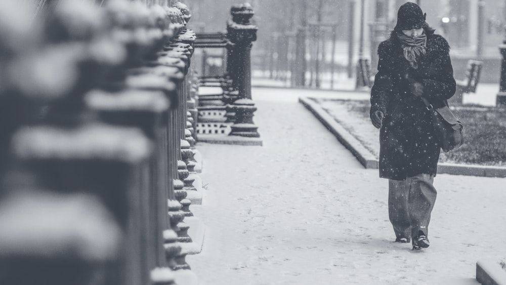 grayscale photo of person walking on street
