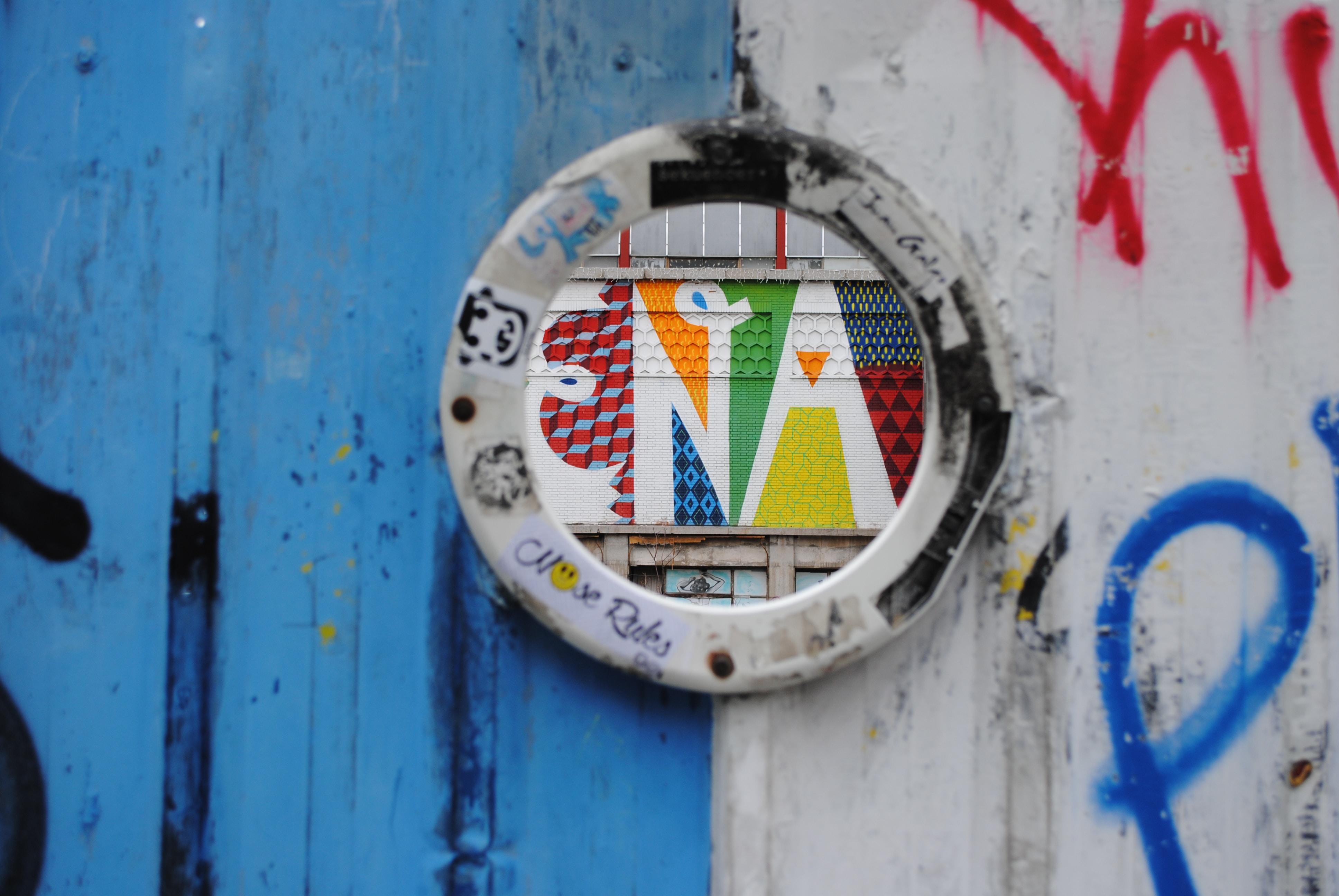 Colorful graffiti typography in round window surrounded by graffiti tags at Mercado de la Cebada