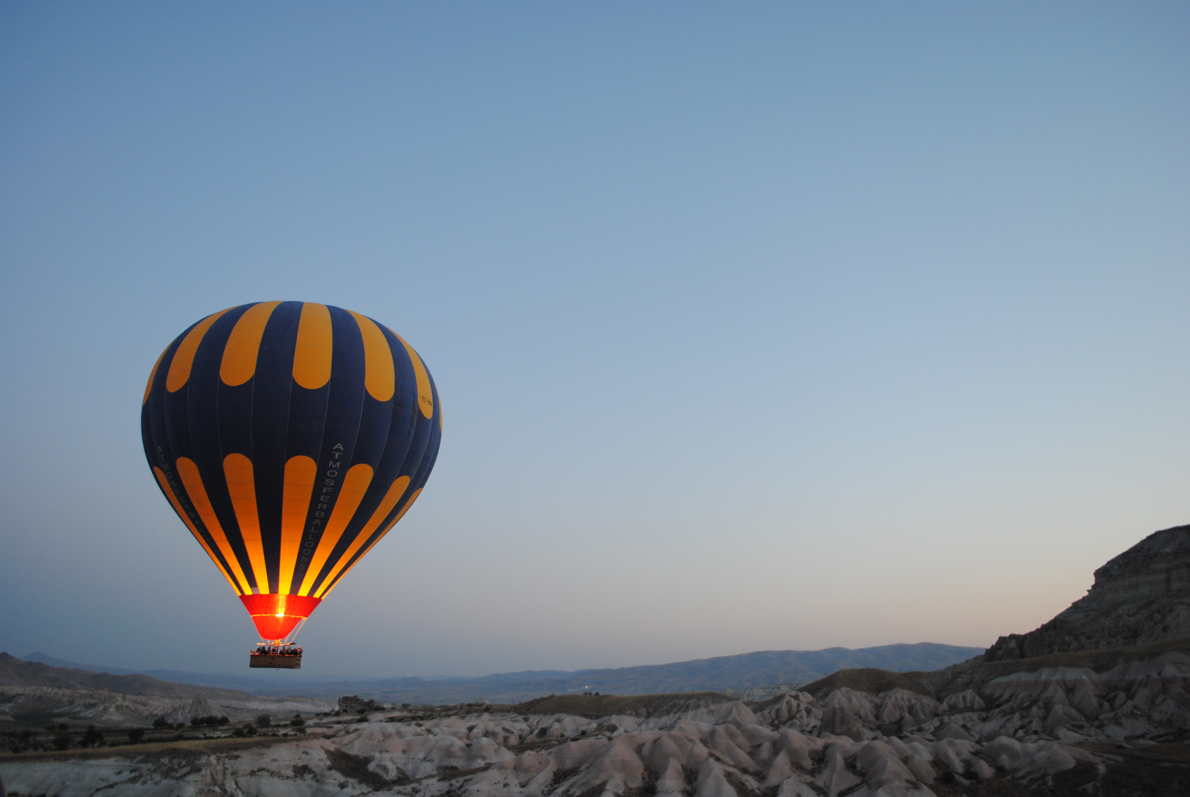 Hot air balloon floats over a mountain landscape at dusk