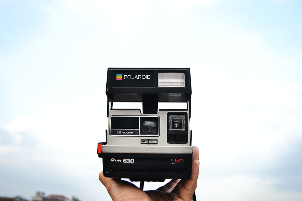 person holding black and gray Polaroid 630 instant camera
