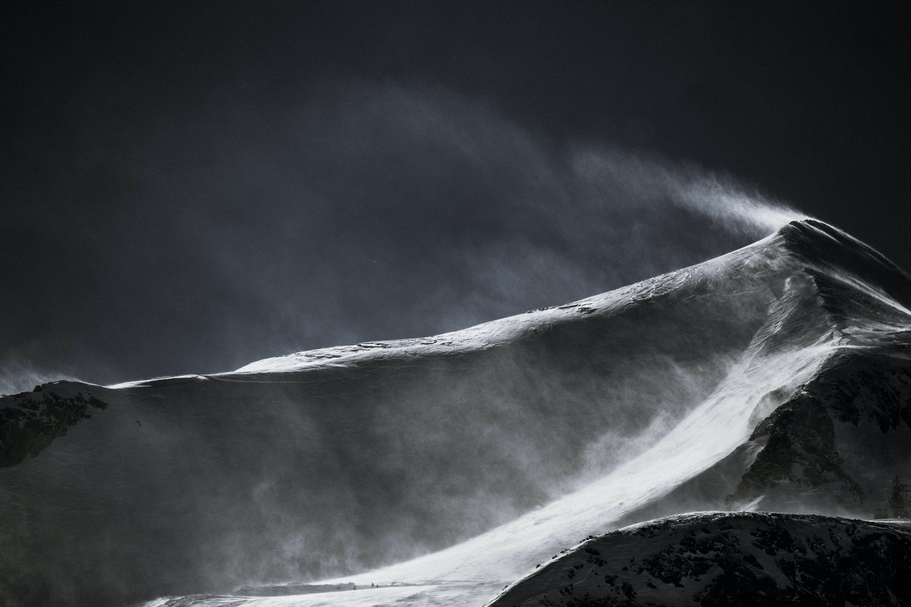 Black and white drone shot of a mountain peak covered in snow