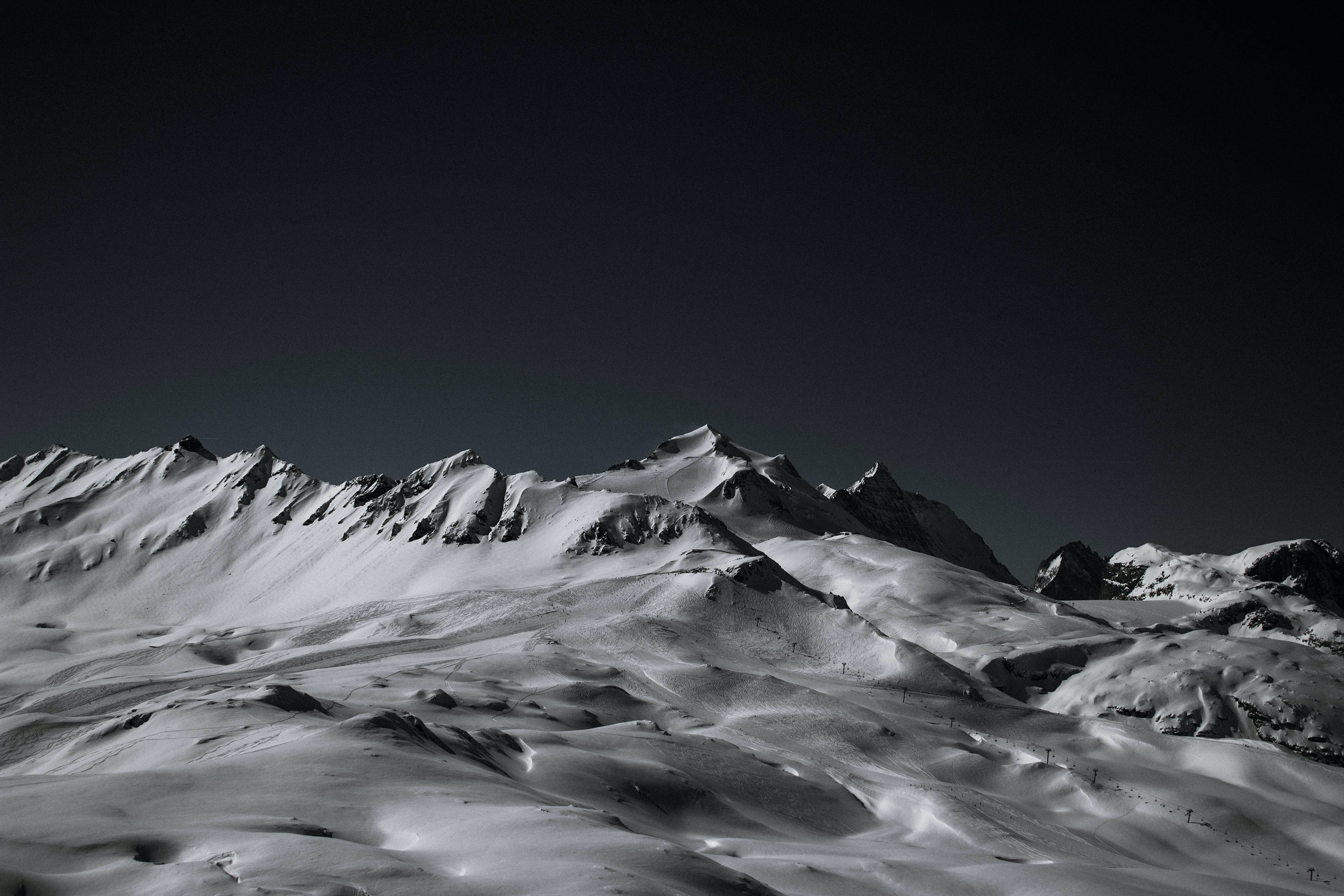 A dark look at a snow covered mountain.