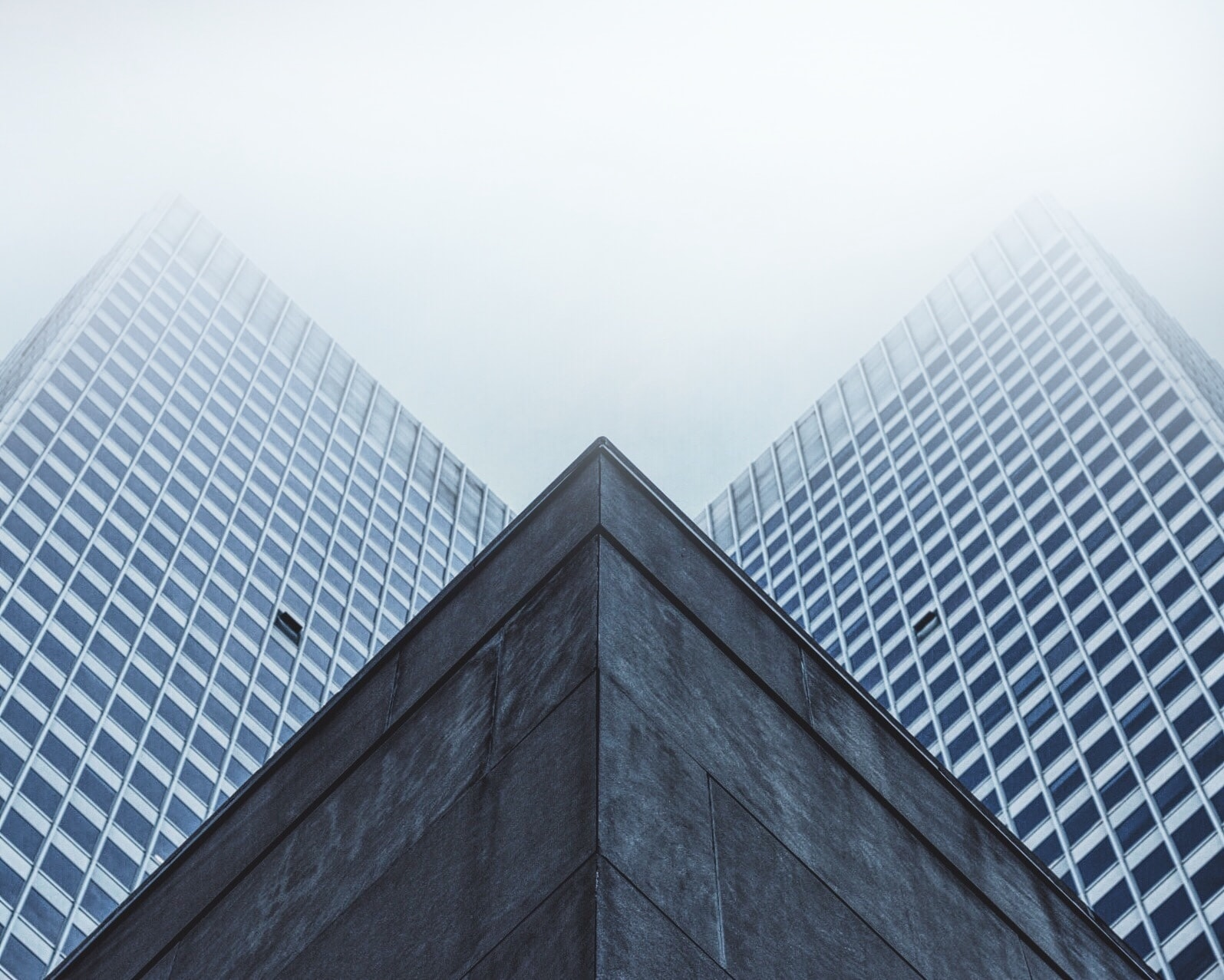 Two high-rise wings towering above the roof of a lower building in Montreal