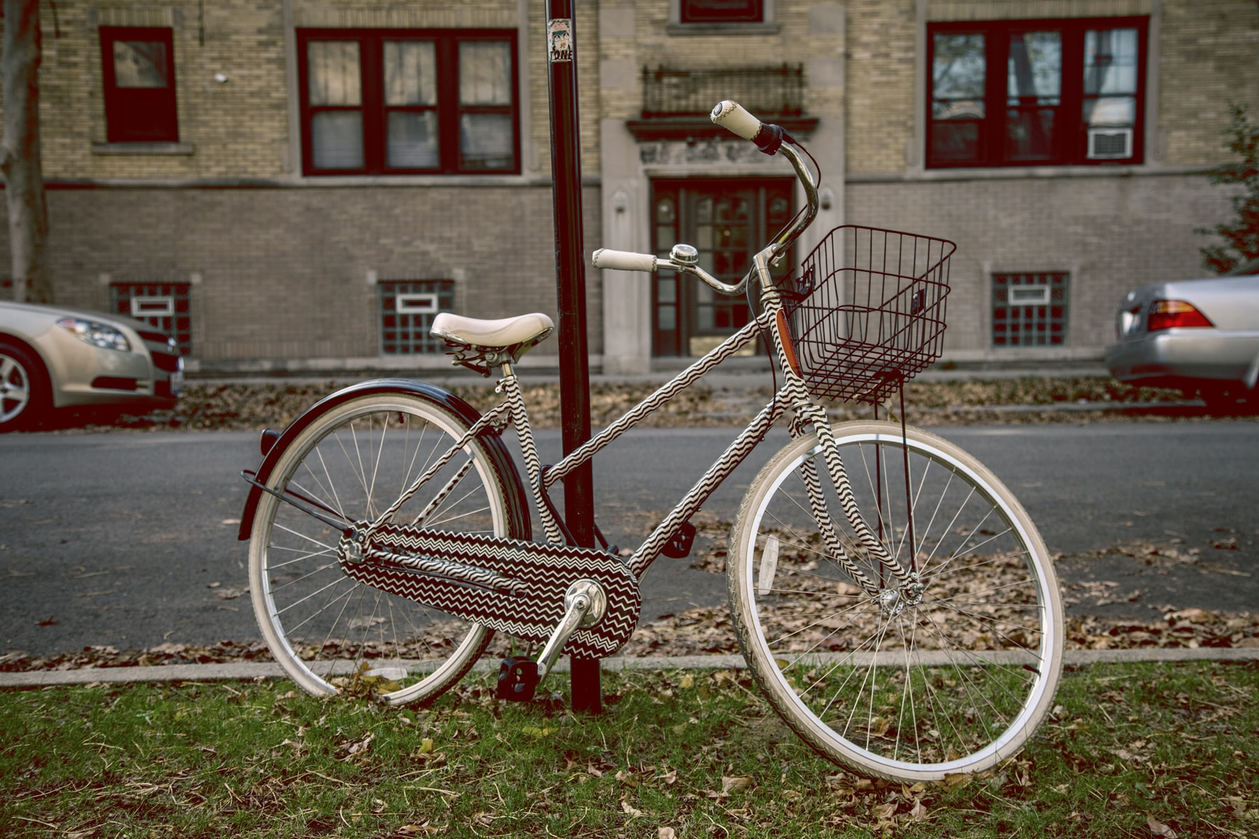 White bicycle with a basket leans against post on a street in Chicago