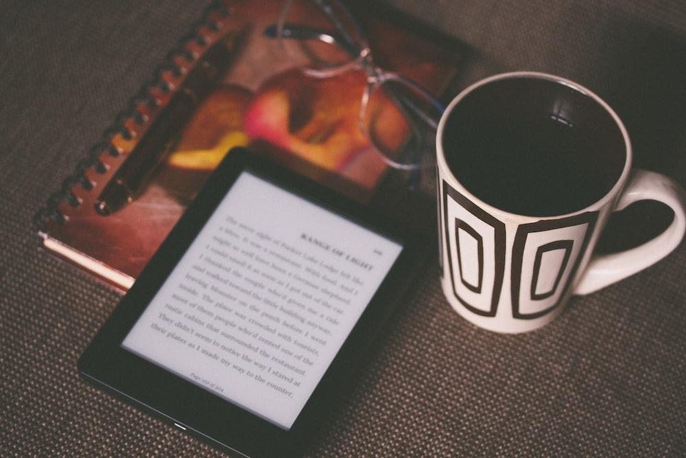 black E-book reader beside white and black mug