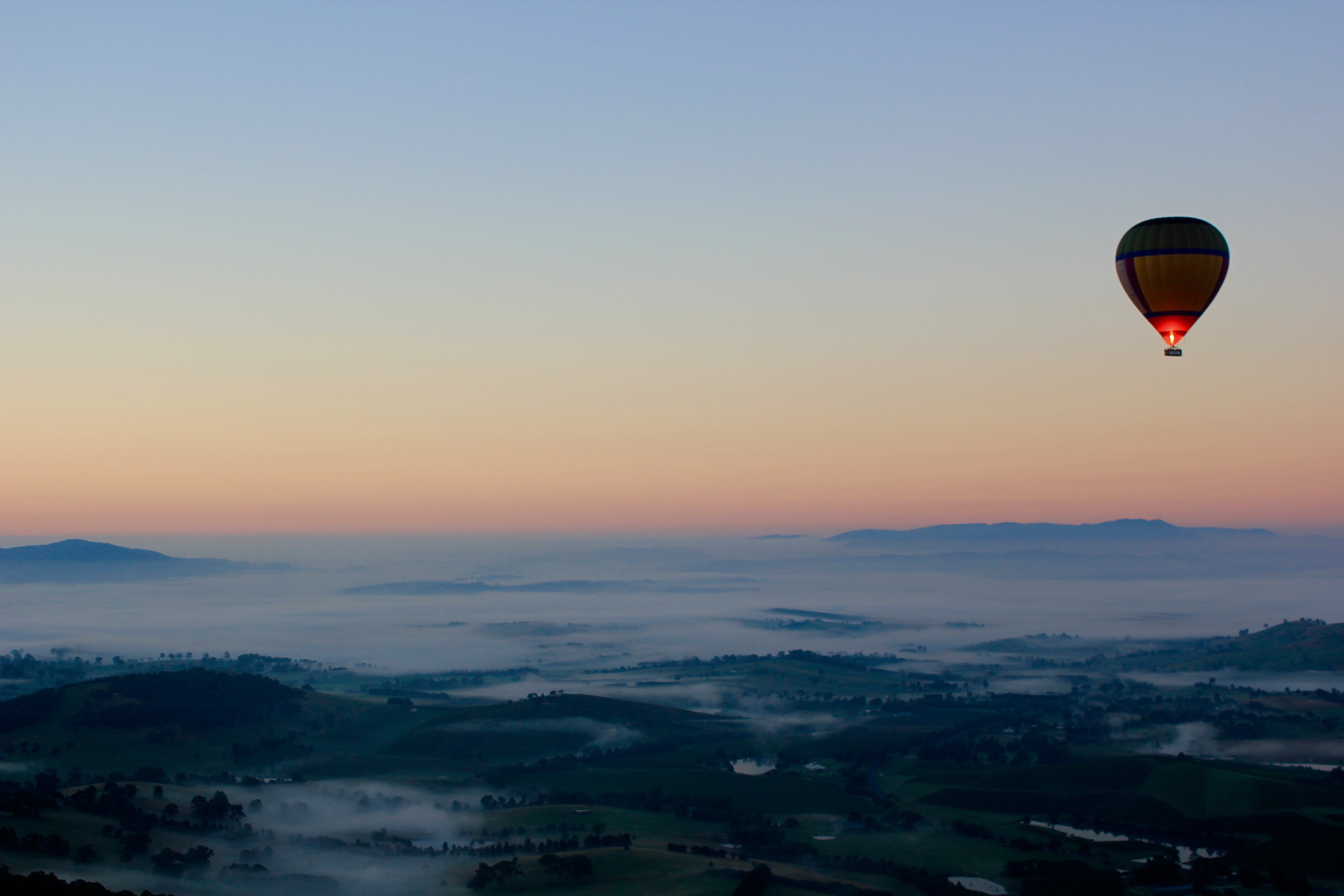 Hot air balloon rides over a misty mountainscape in Yarra Valley
