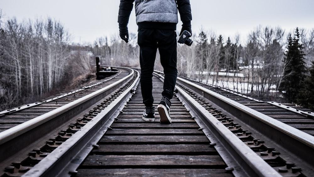 man waking on train rail