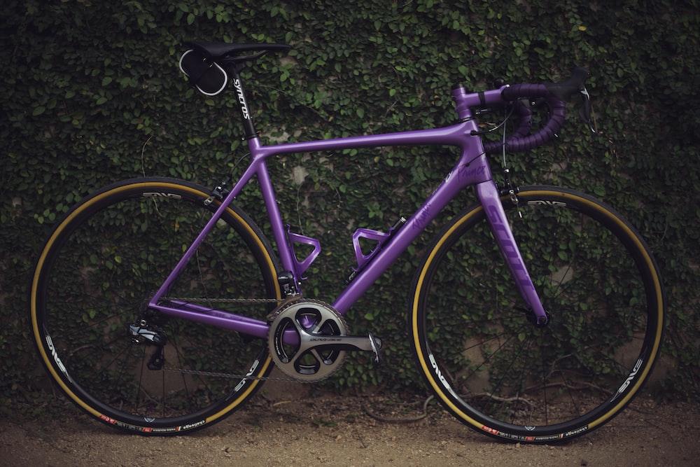 purple road bike near wall