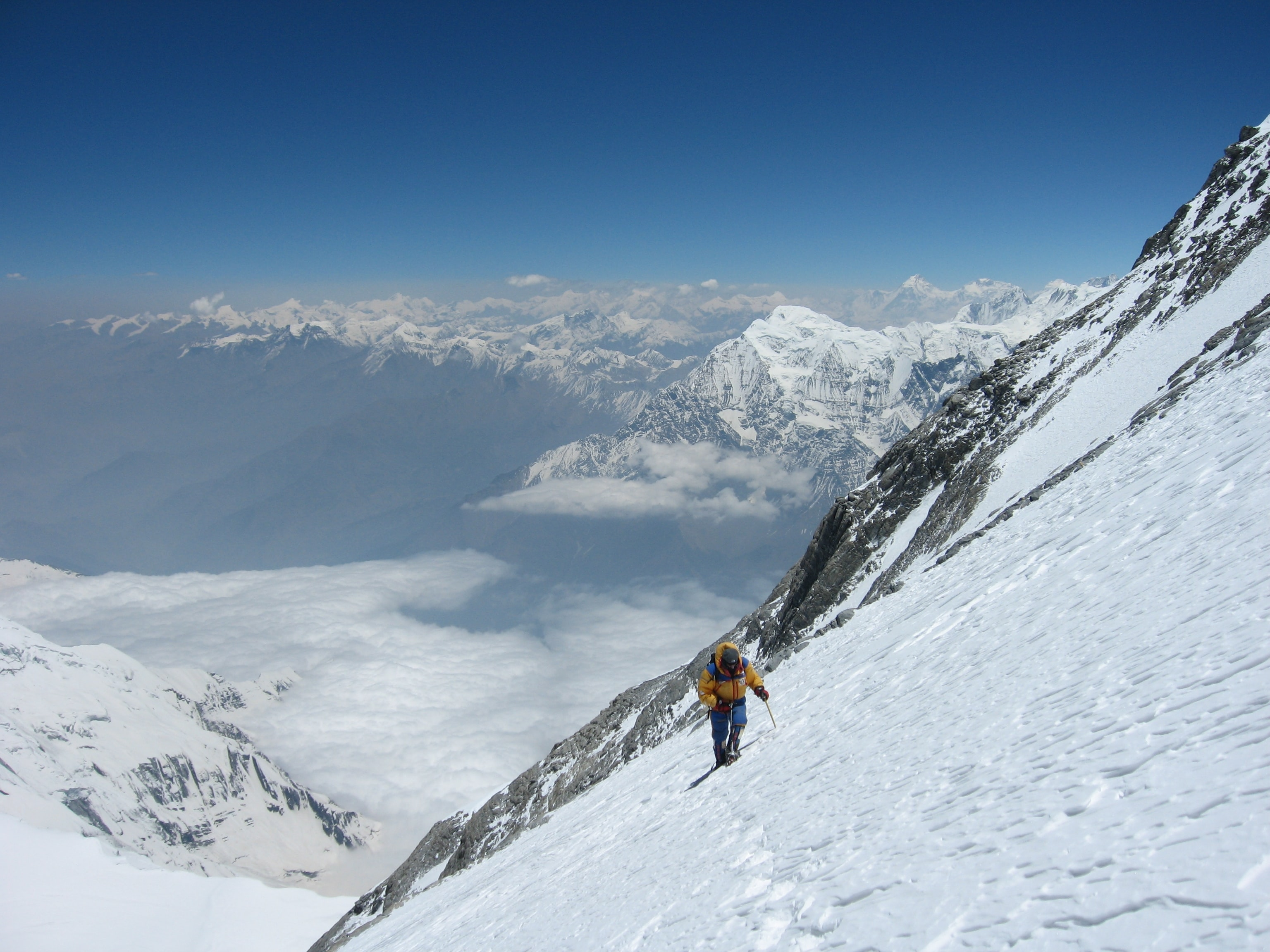 Extreme hiker ascends a snow covered mountain landscape