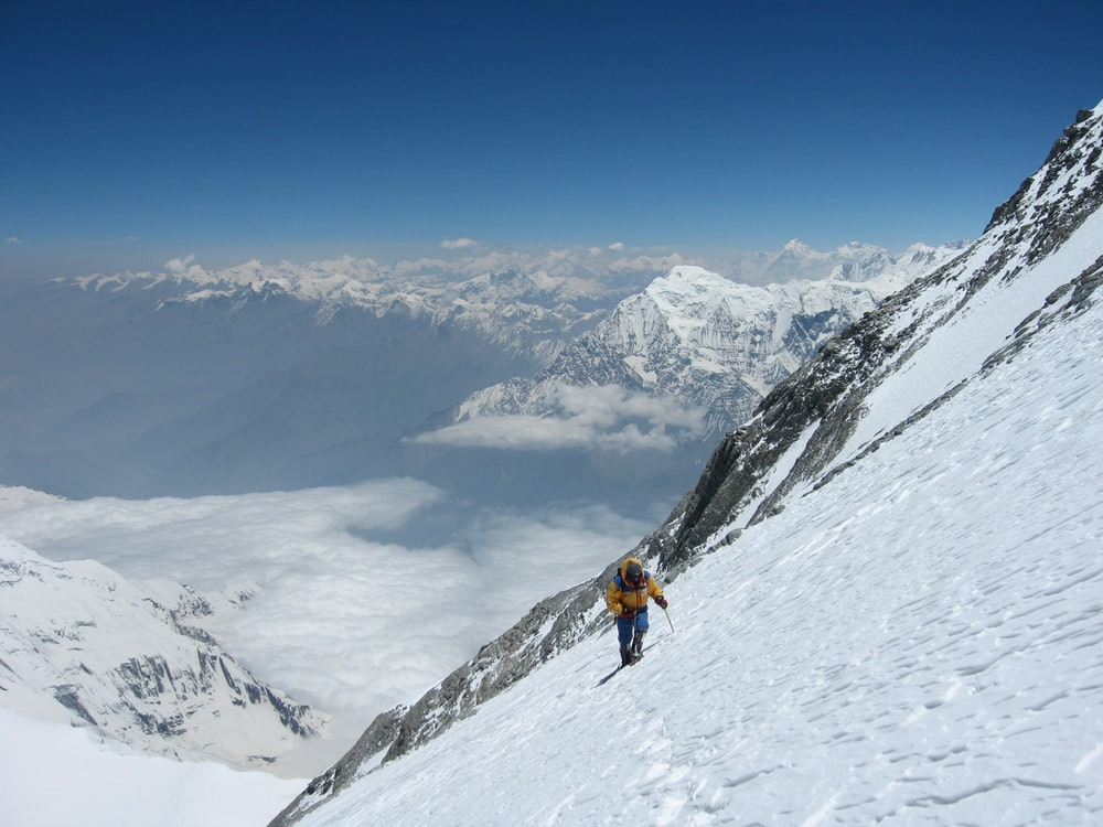 person climbing snow-covered mountain during daytime