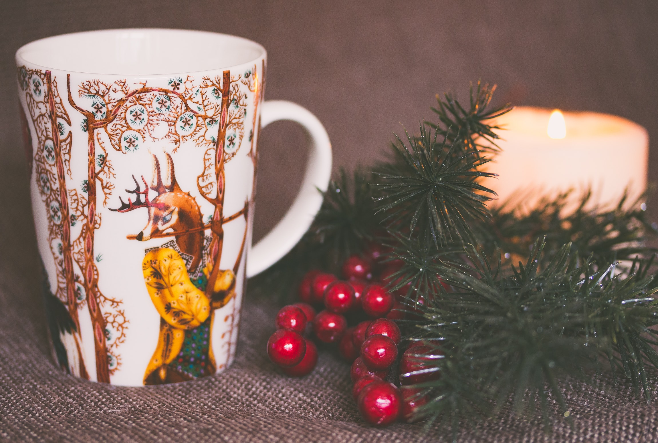 white and brown print ceramic mug near red mistletoe and candle