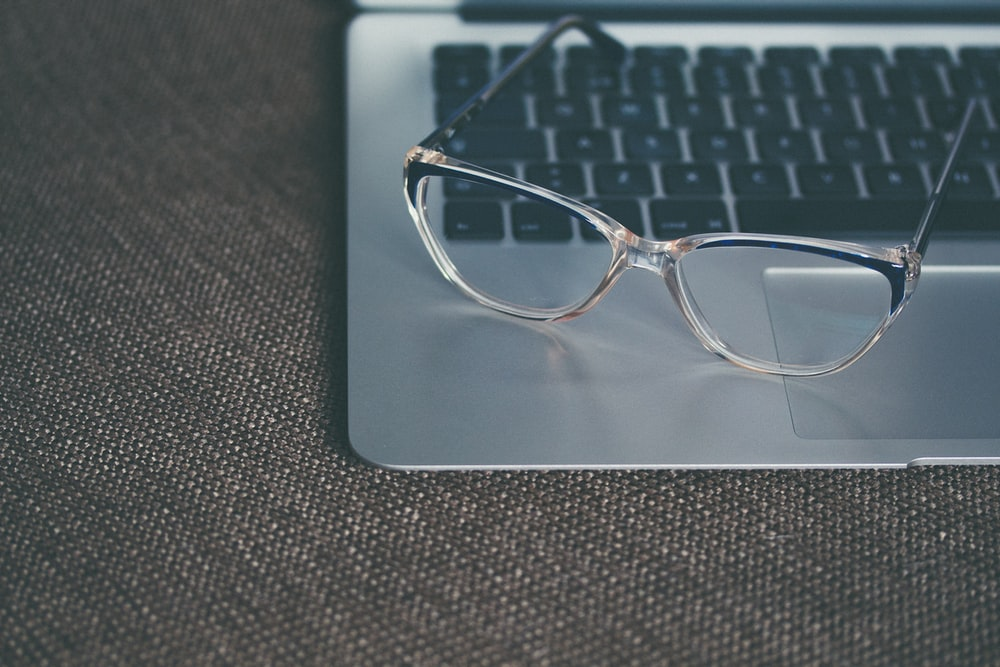 A pair of glasses on a MacBook keyboard