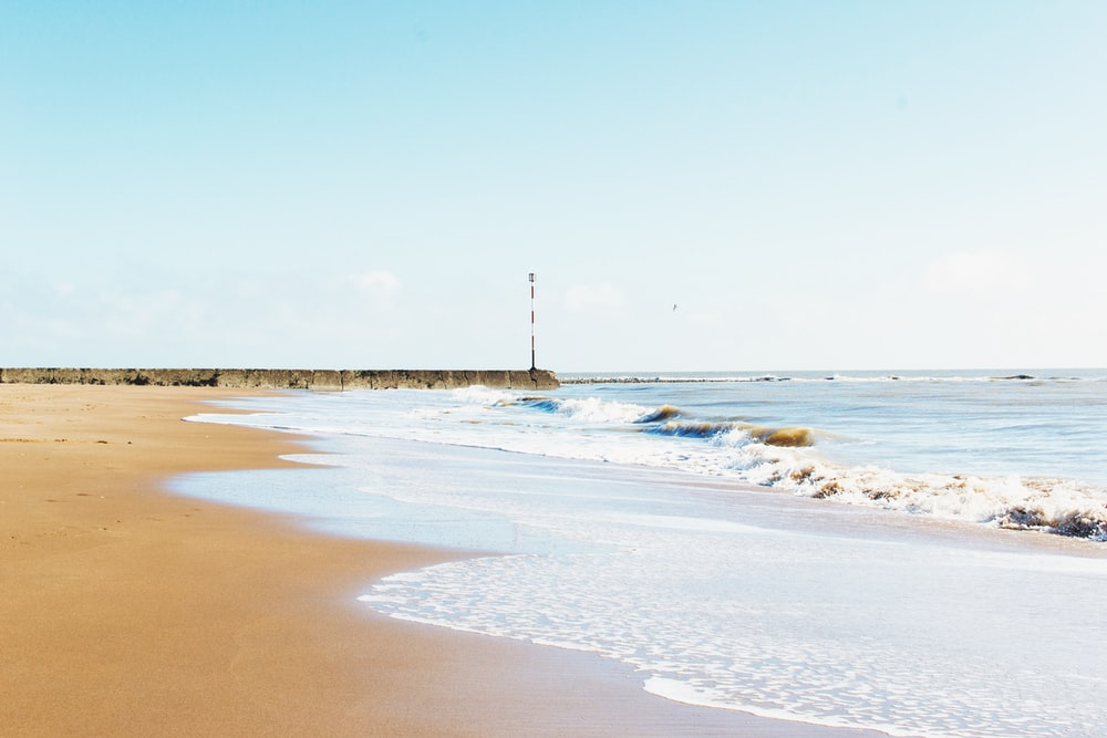 brown sand beach and ocean waves during daytime