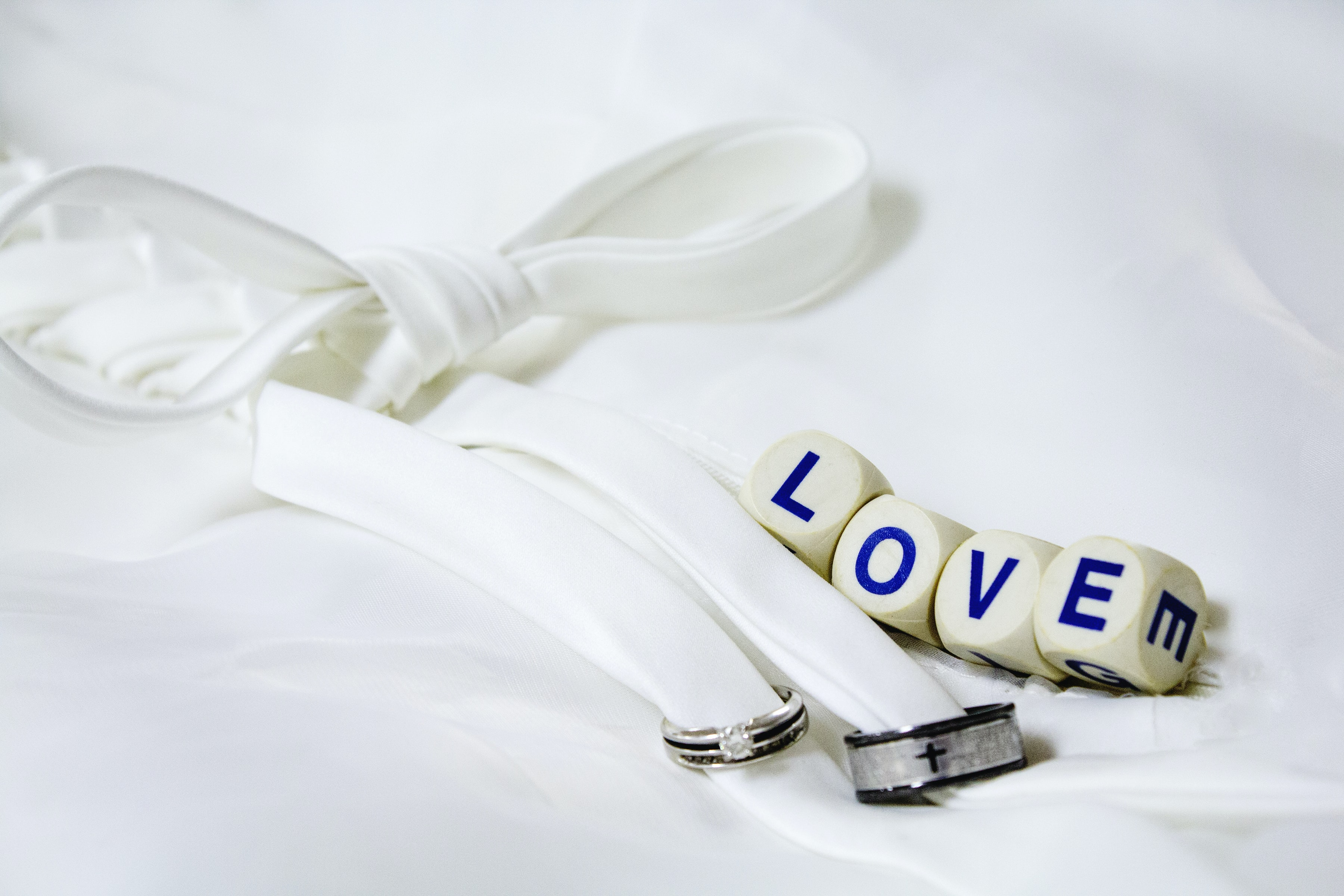 """White material tied in a bow, with little cubes that say """"Love."""""""