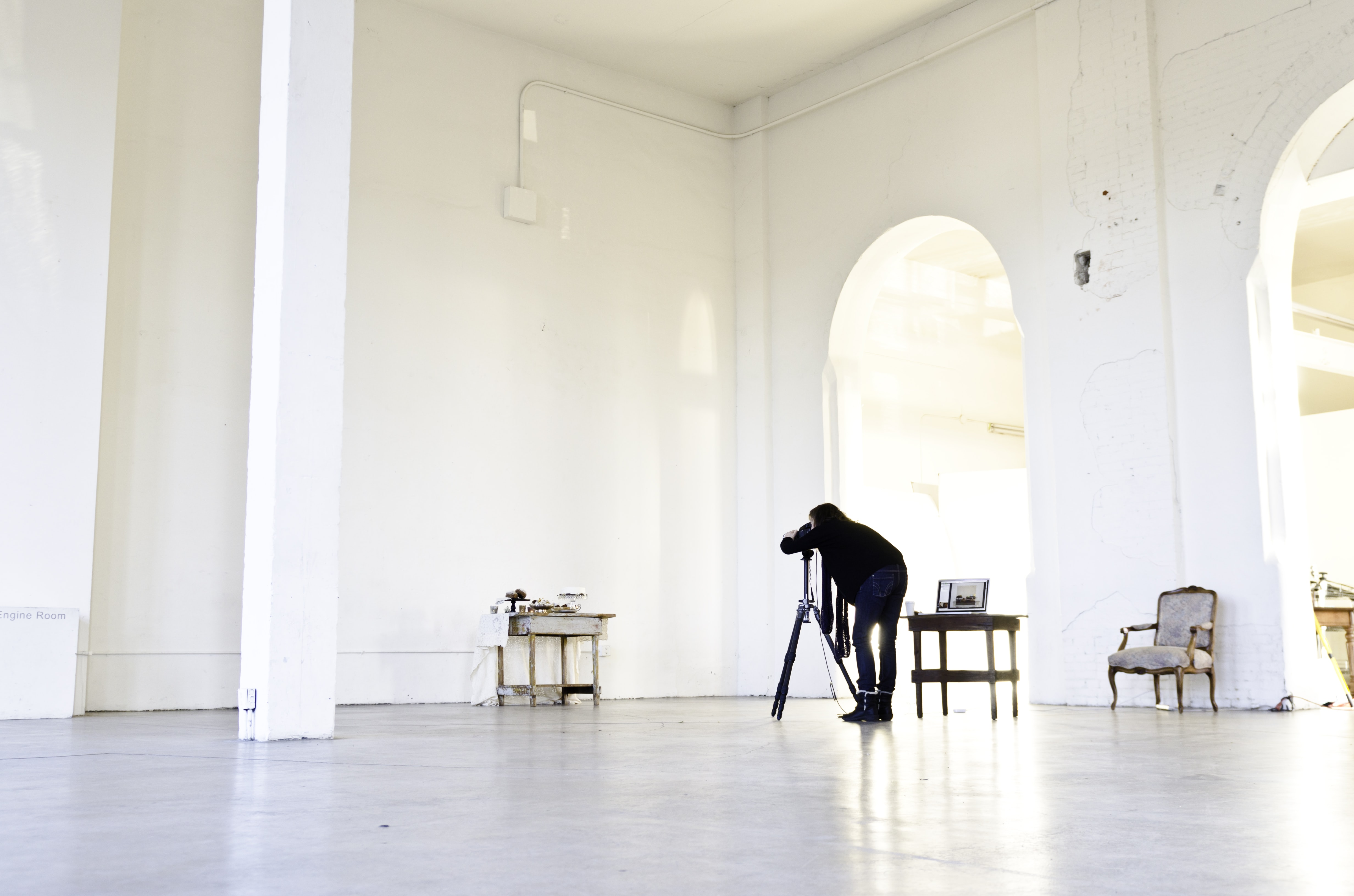 A photographer with at tripod takes a picture of a still life in a white building with tall ceilings and arches