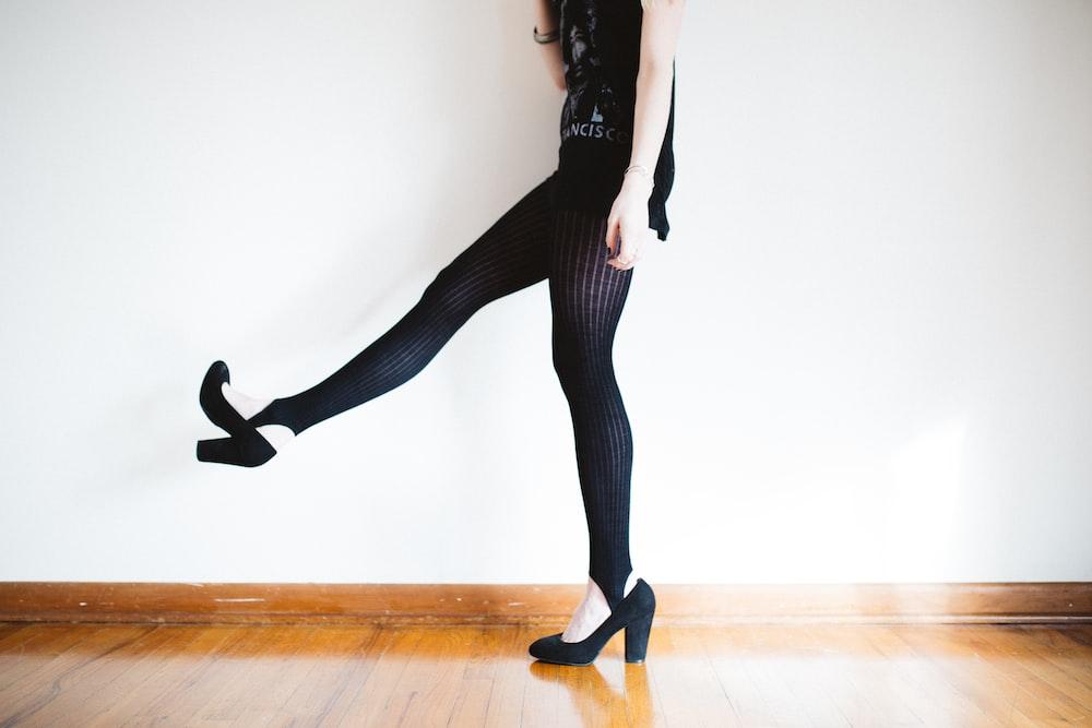 woman raising her right leg near wall