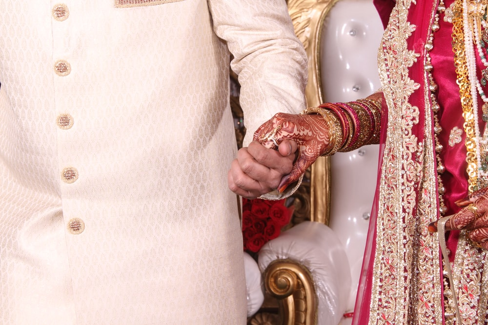 Bride in red and gold dress holds hands with groom in India