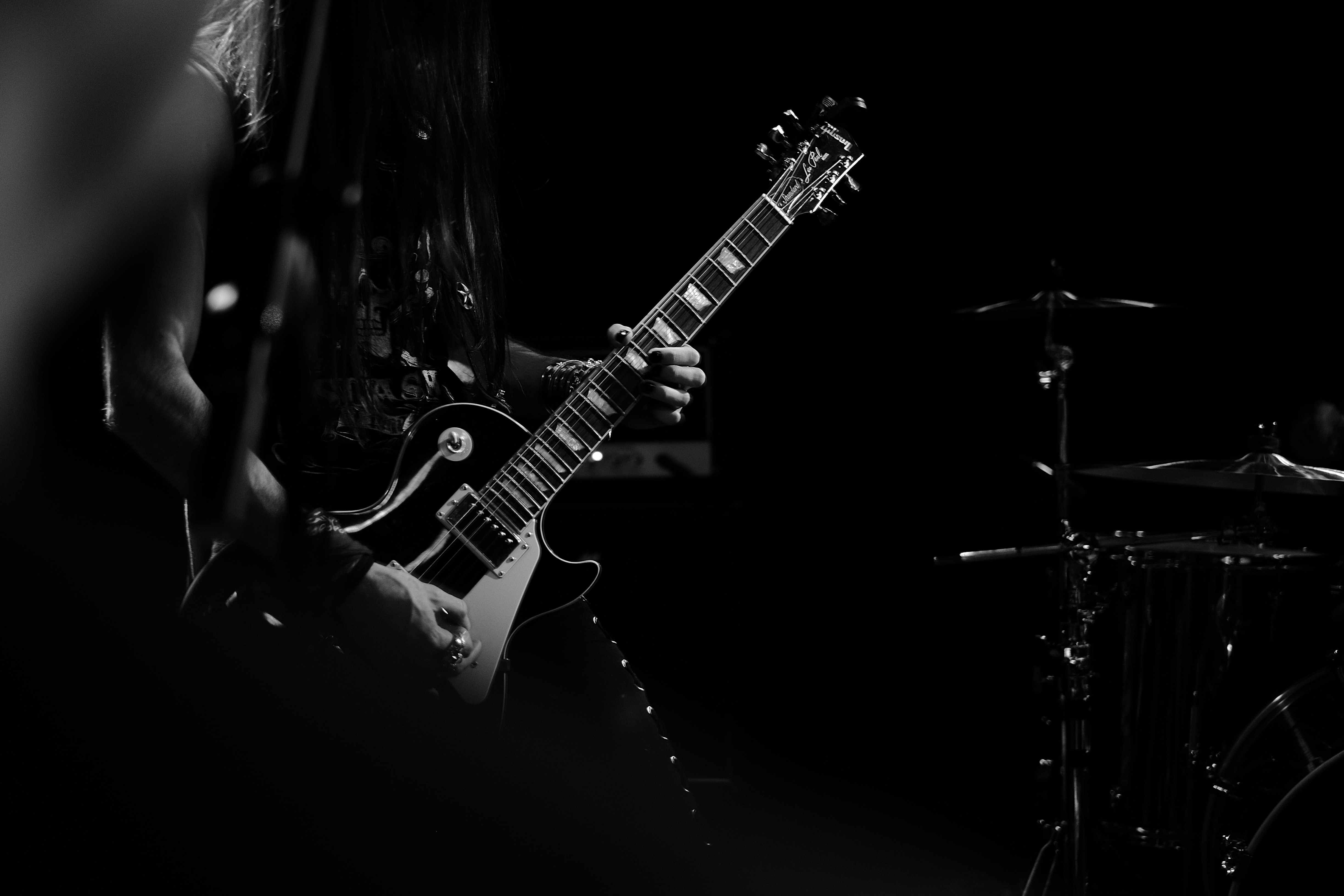 A black-and-white shot of a bass guitarist on stage