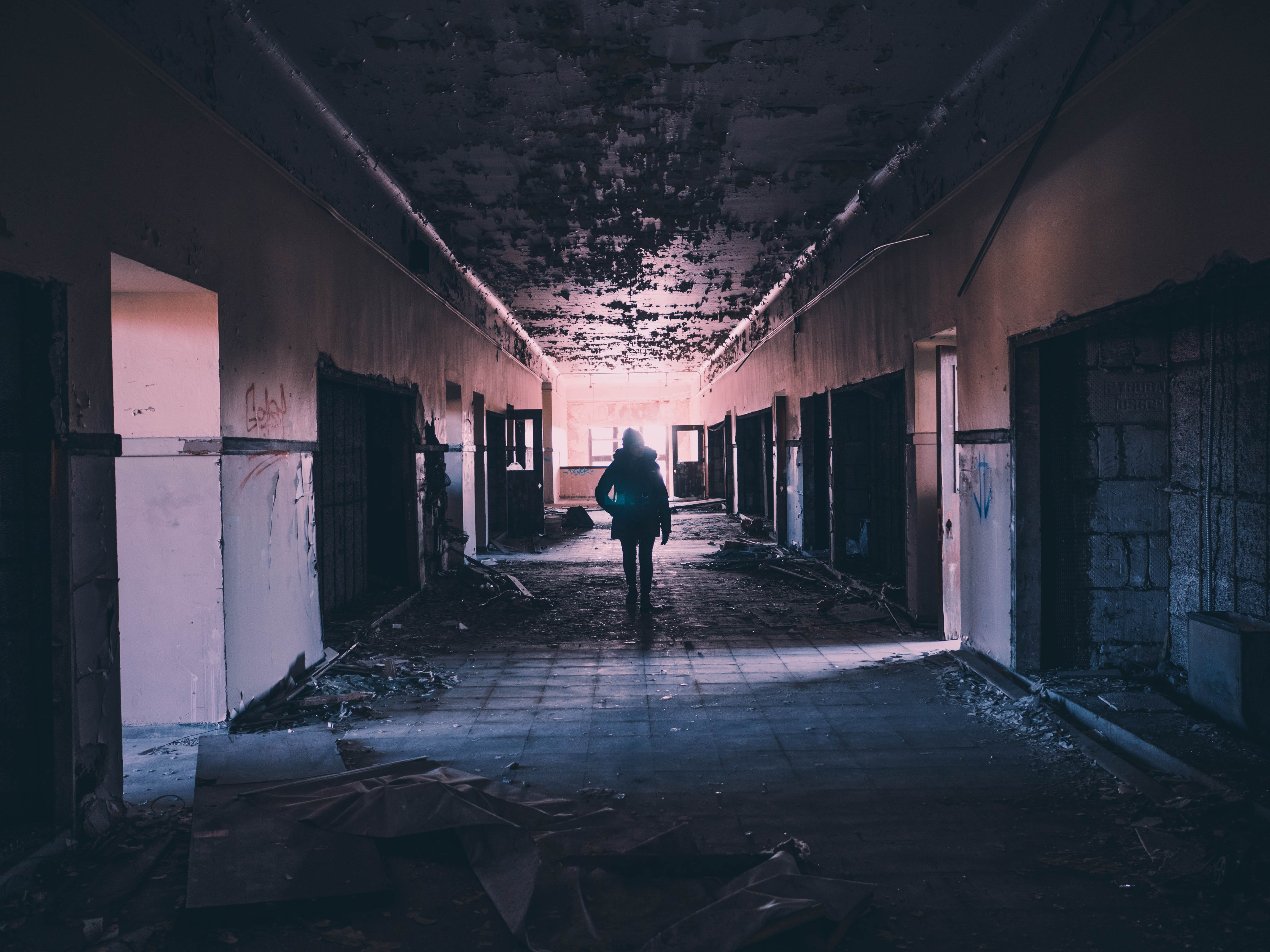 A person walking inside a dimly lit Detroit building at night
