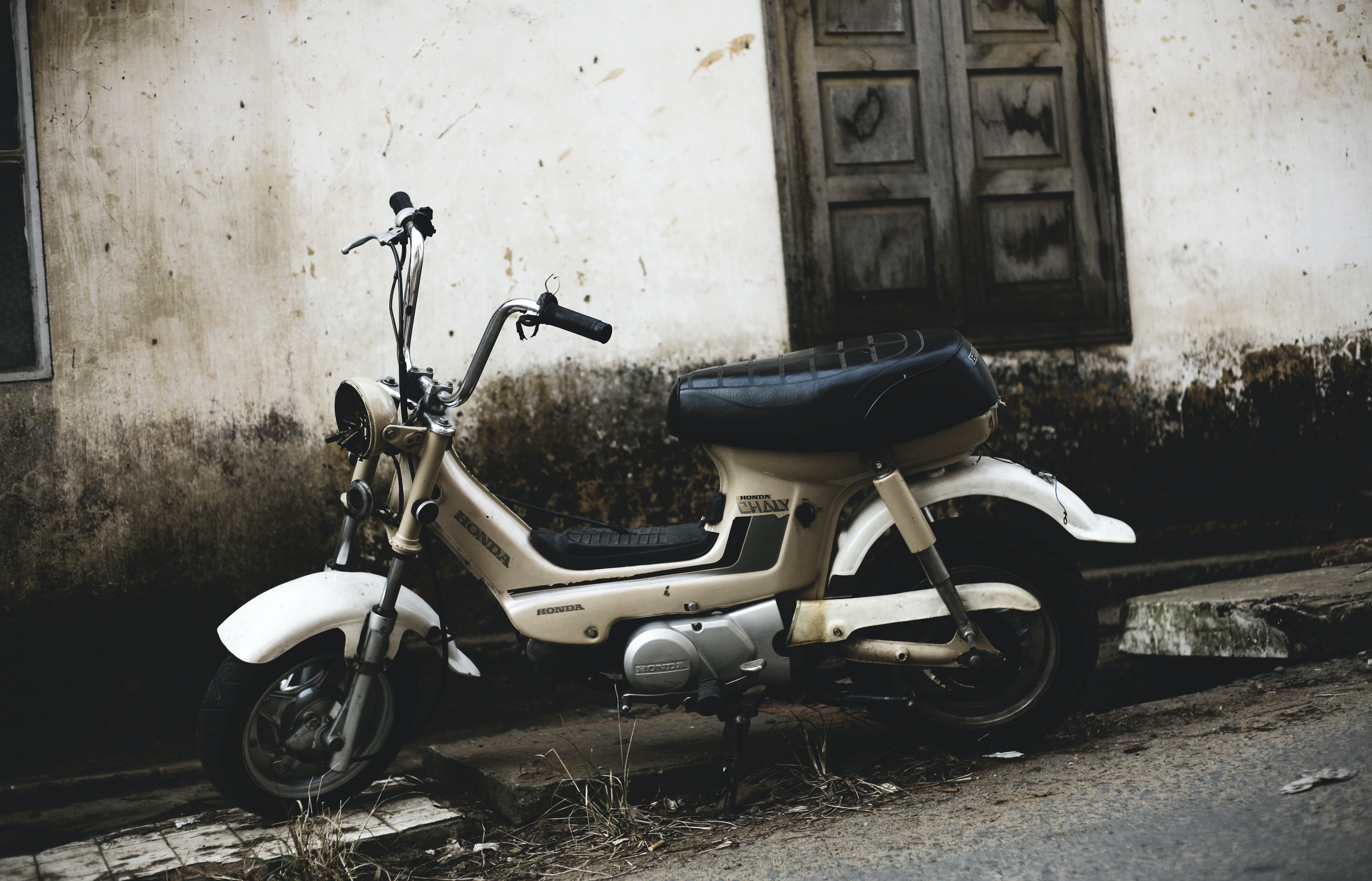 Sepia photo of white moped on a street near wooden window
