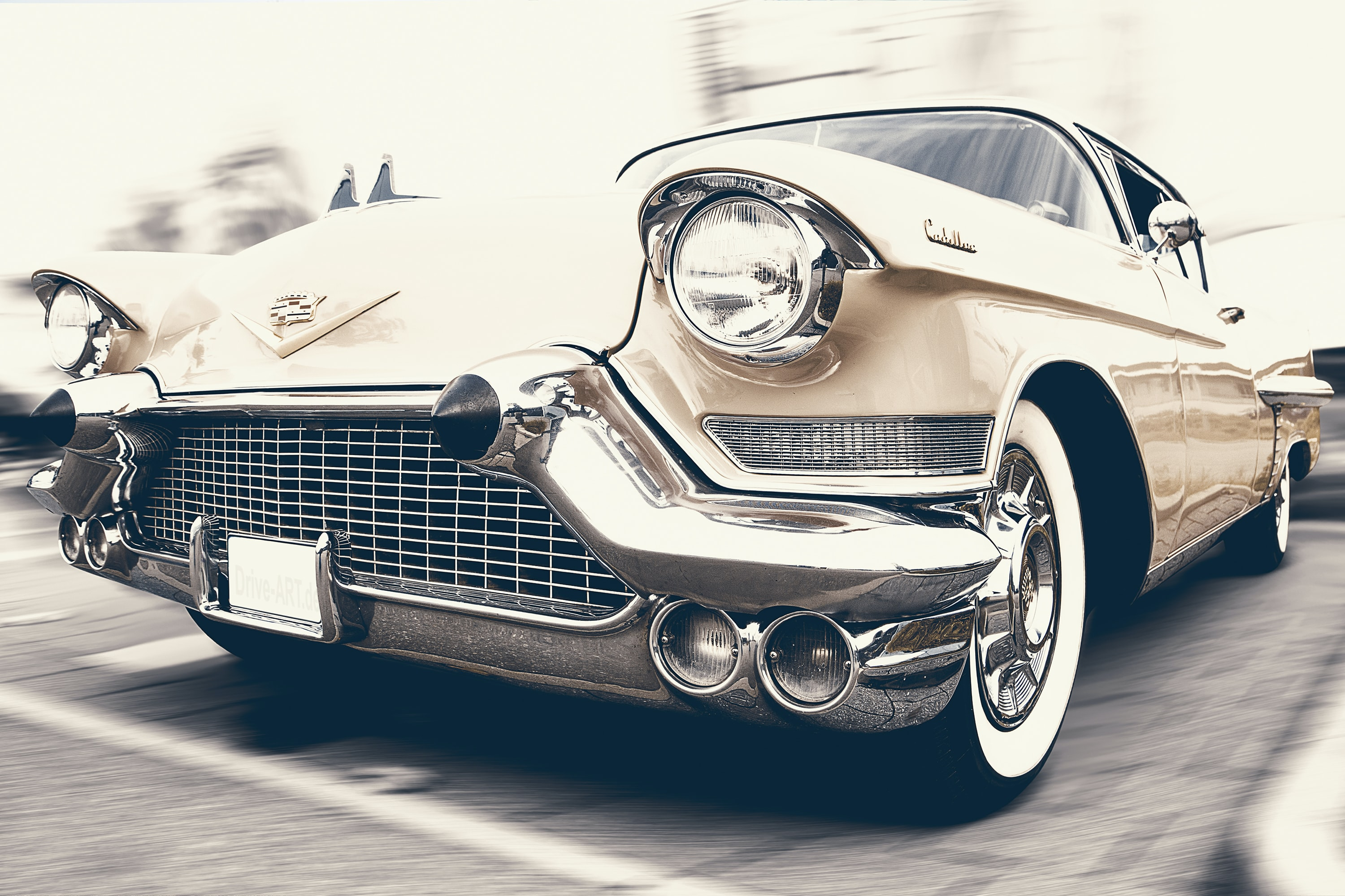 Close up shot of vintage beige Cadillac with chrome grille parked on pavement