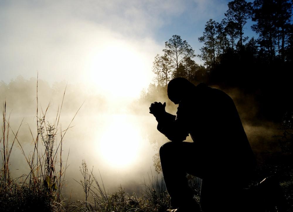 silhouette of kneeling man
