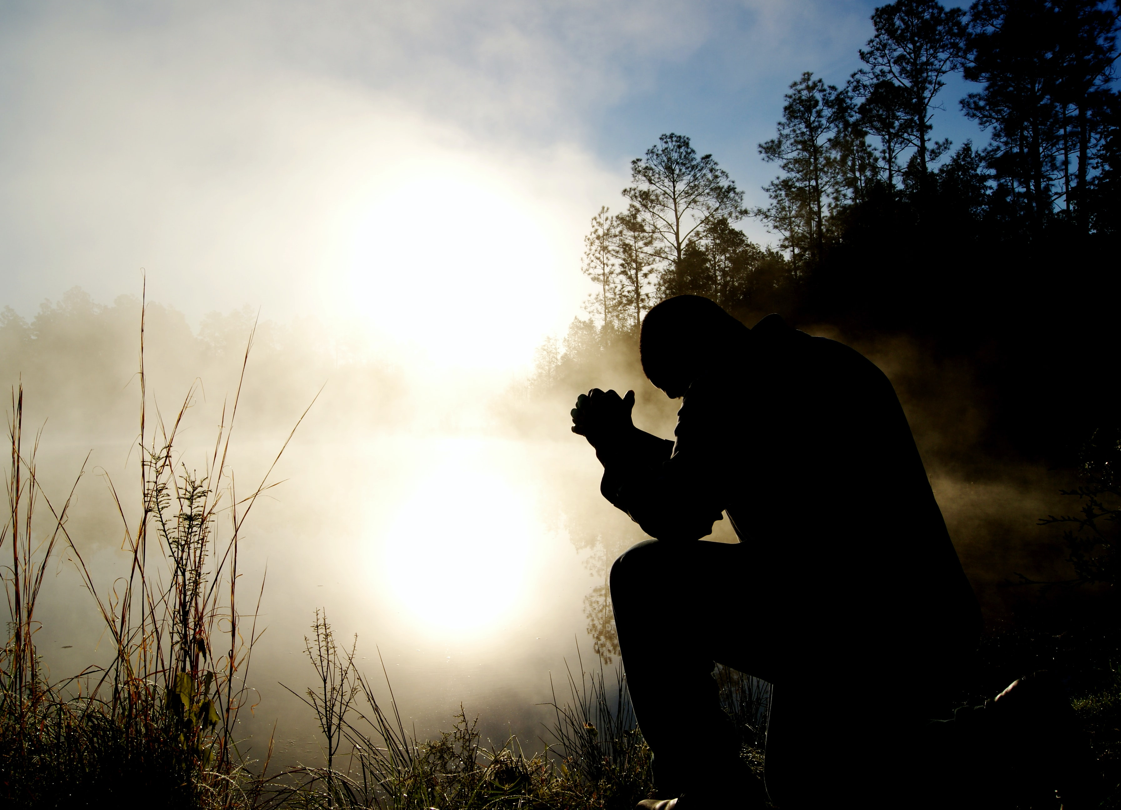 A silhouette of a man sitting outside with his hands together in prayer.