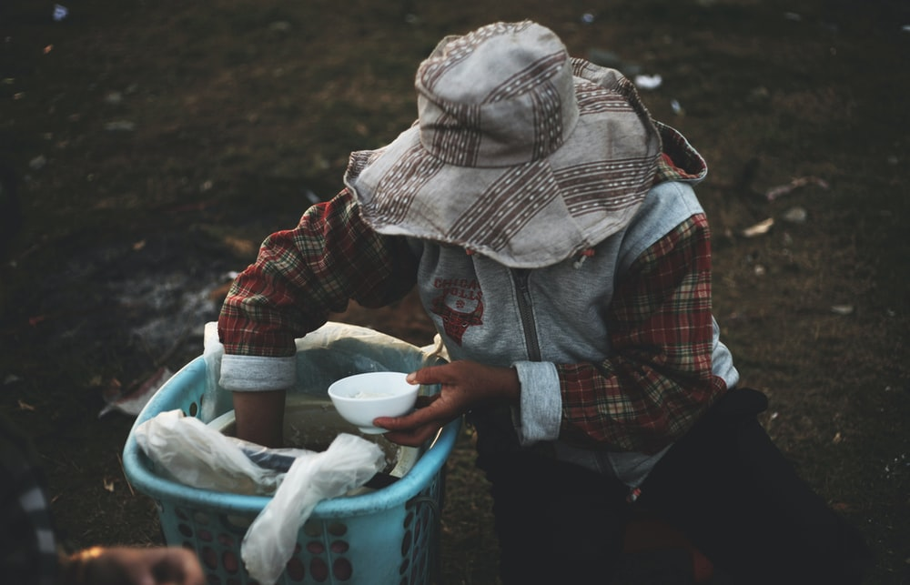person in hat holding bowl while hand inside basket