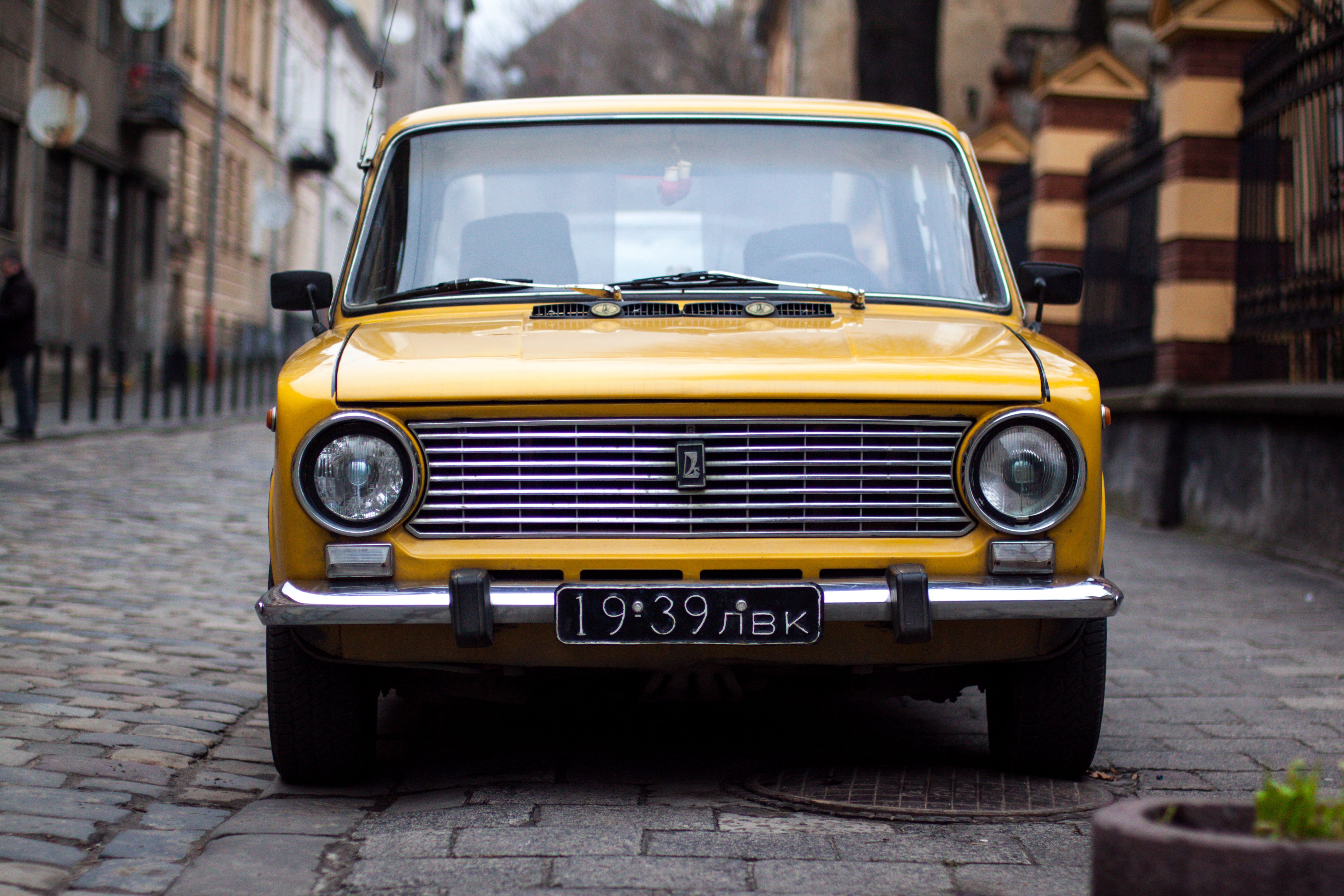 An old vintage yellow car parked on a cobblestone street