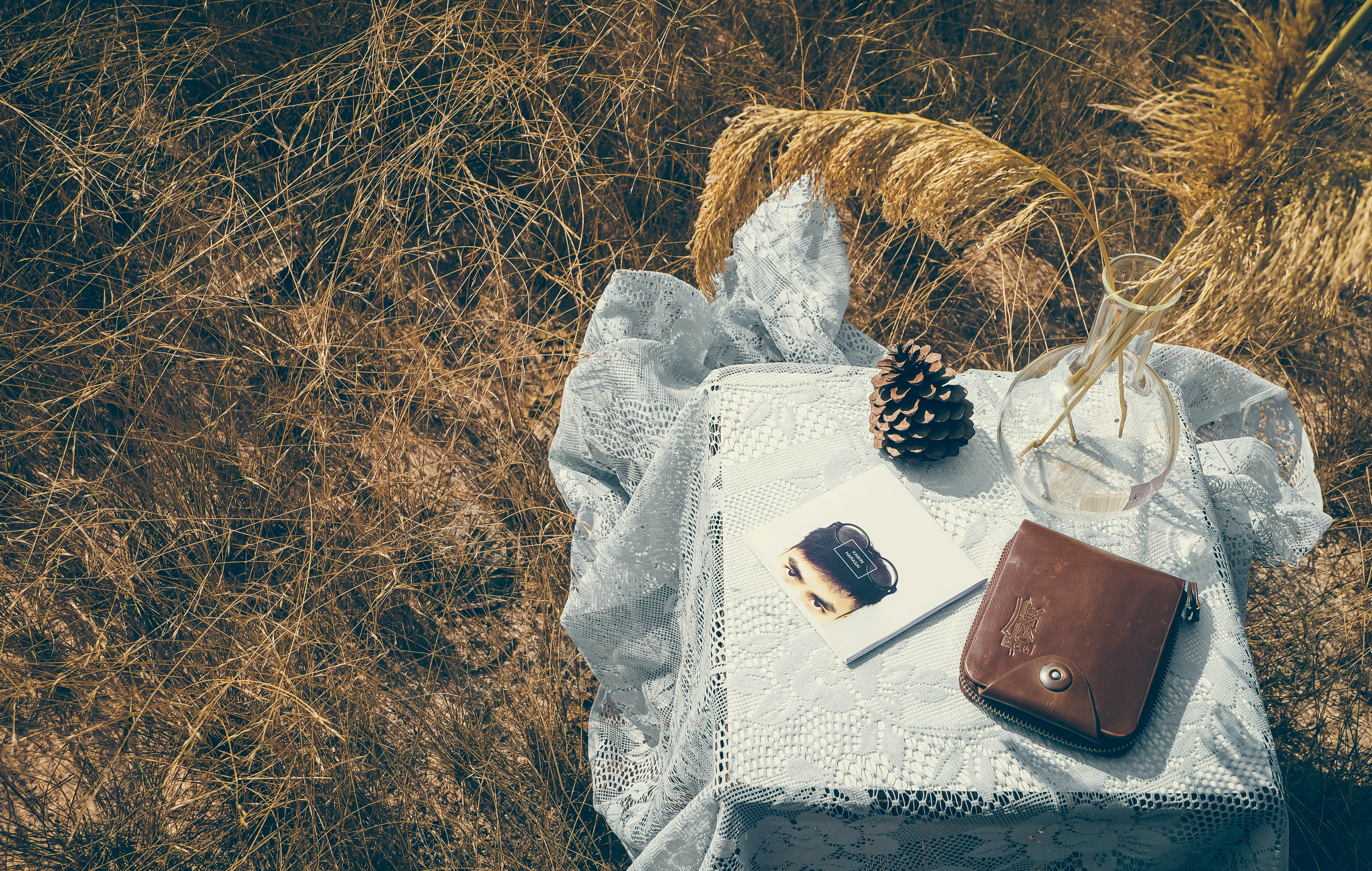 A pine cone, journal, leather bag, and reed diffuser on a lace tablecloth in a wheatfield in Thailand