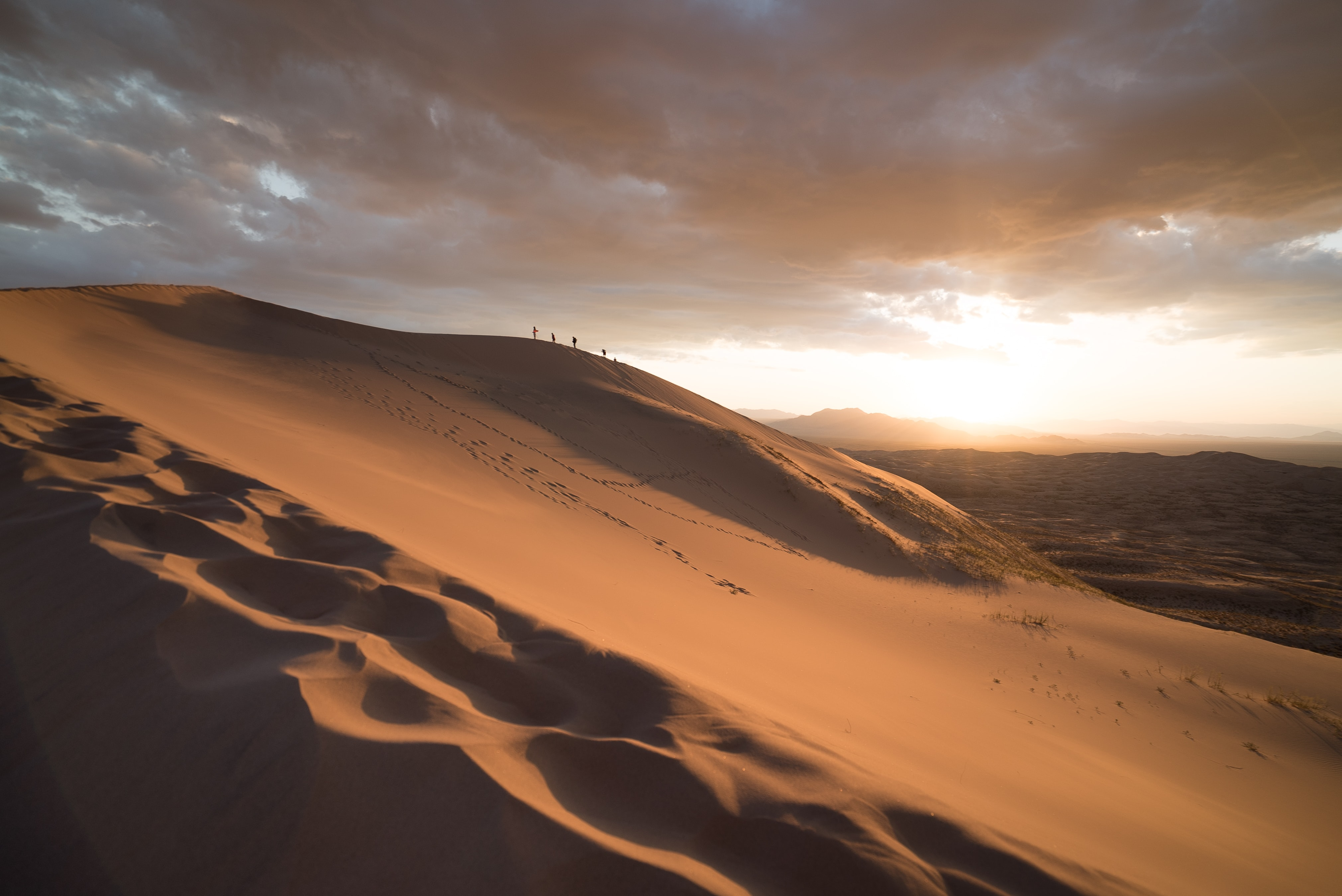 Hikers walking on sand dunes in the Mojave National Preserve