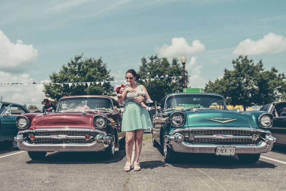 woman carrying child standing between two vintage cars