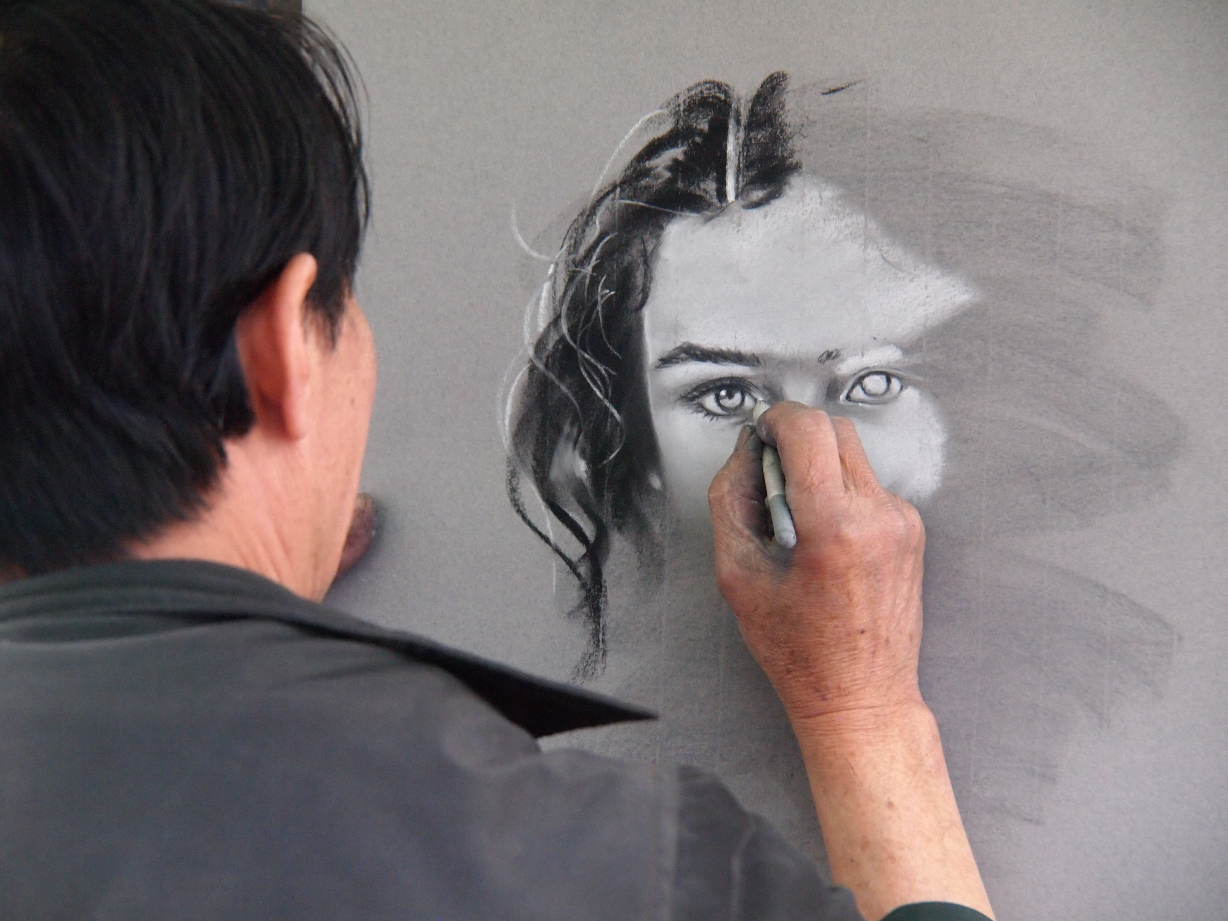 Looking from behind an artist working on an in-progress drawing of a girl's face