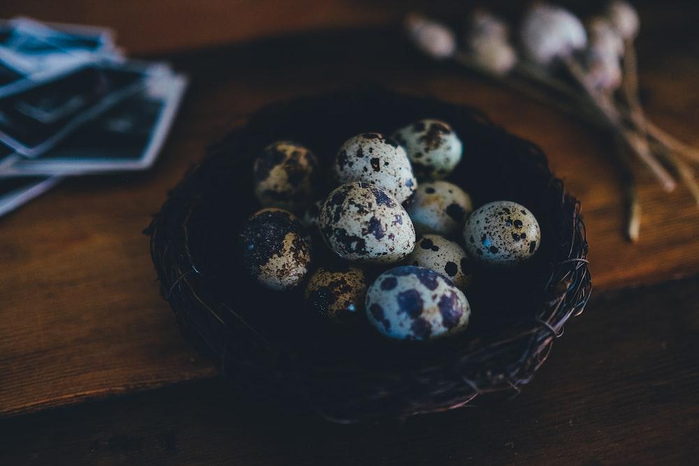 quail eggs on nest on wooden surface