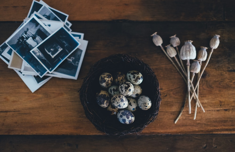 white-and-black quail eggs on brown wicker bowl