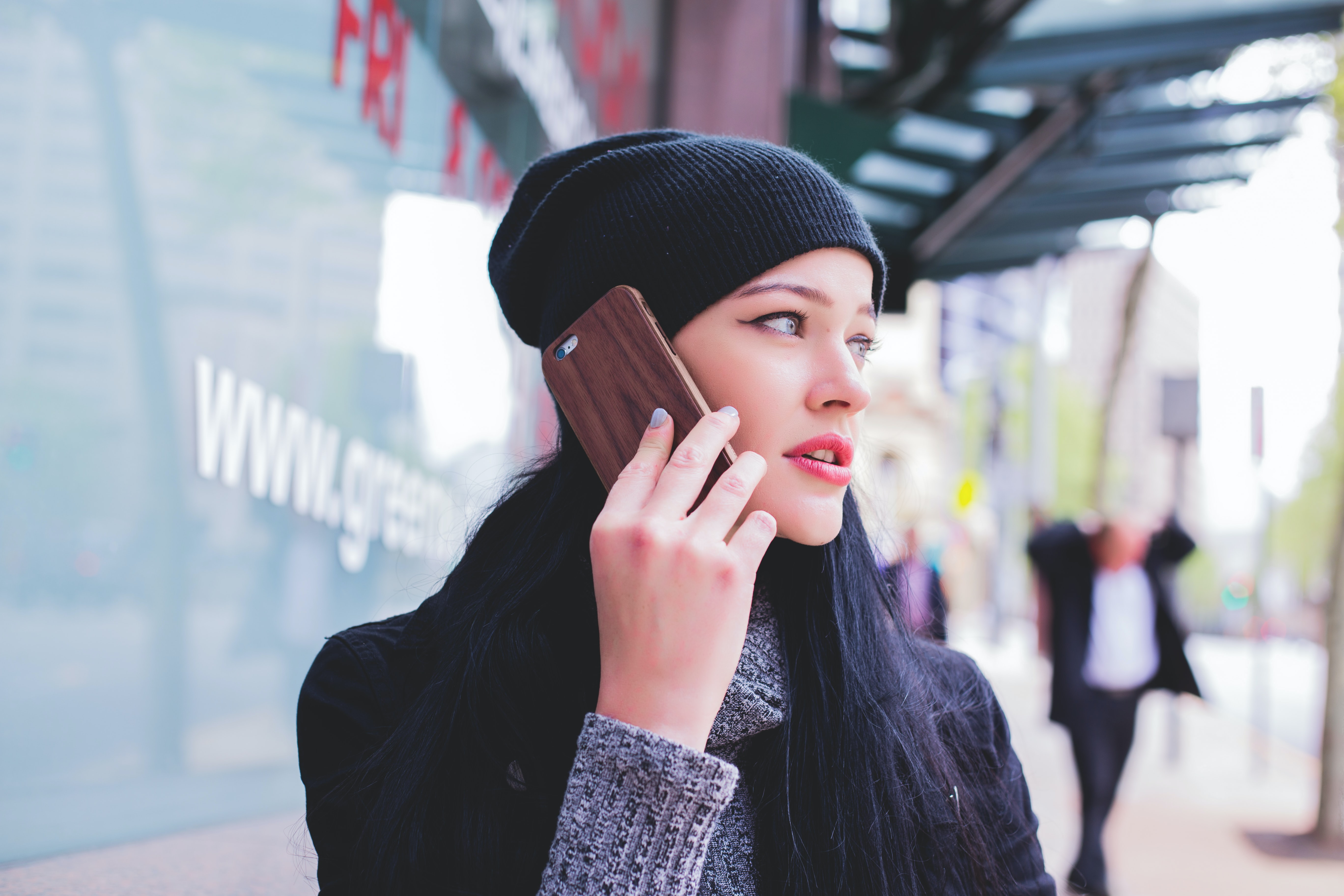 woman wearing beanie with smartphone on ear