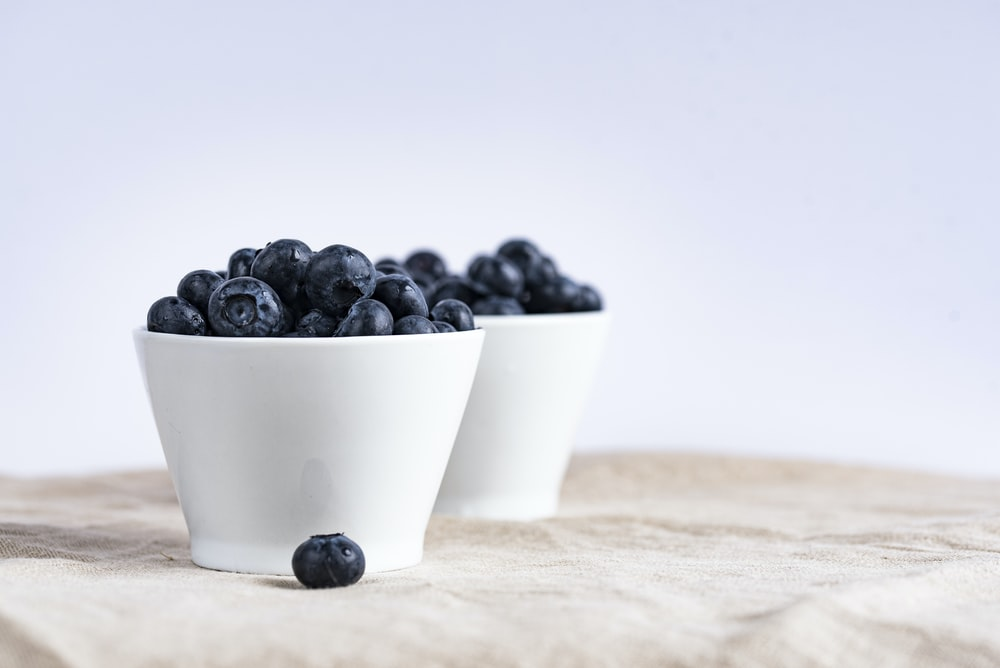 two white ceramic cup filled with blueberries fruit place on brown textile