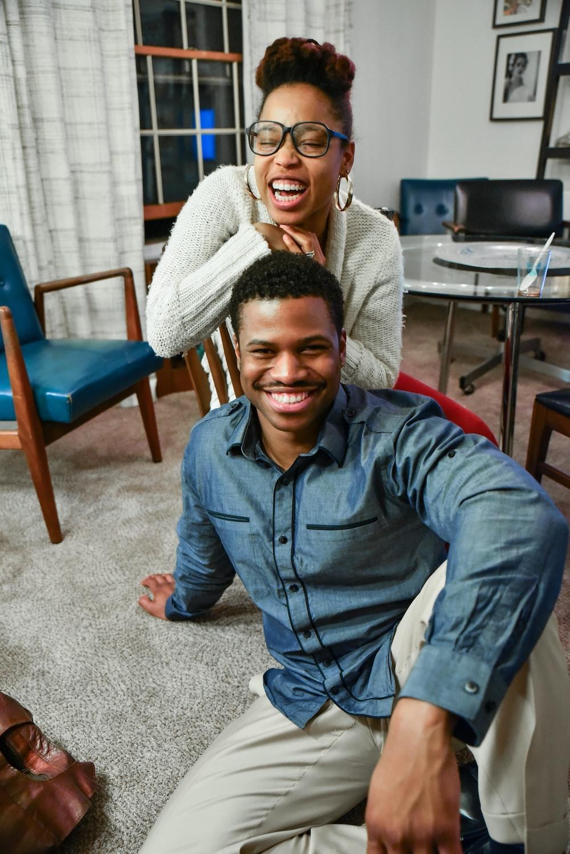 man sitting on floor beside woman smiling inside white painted room