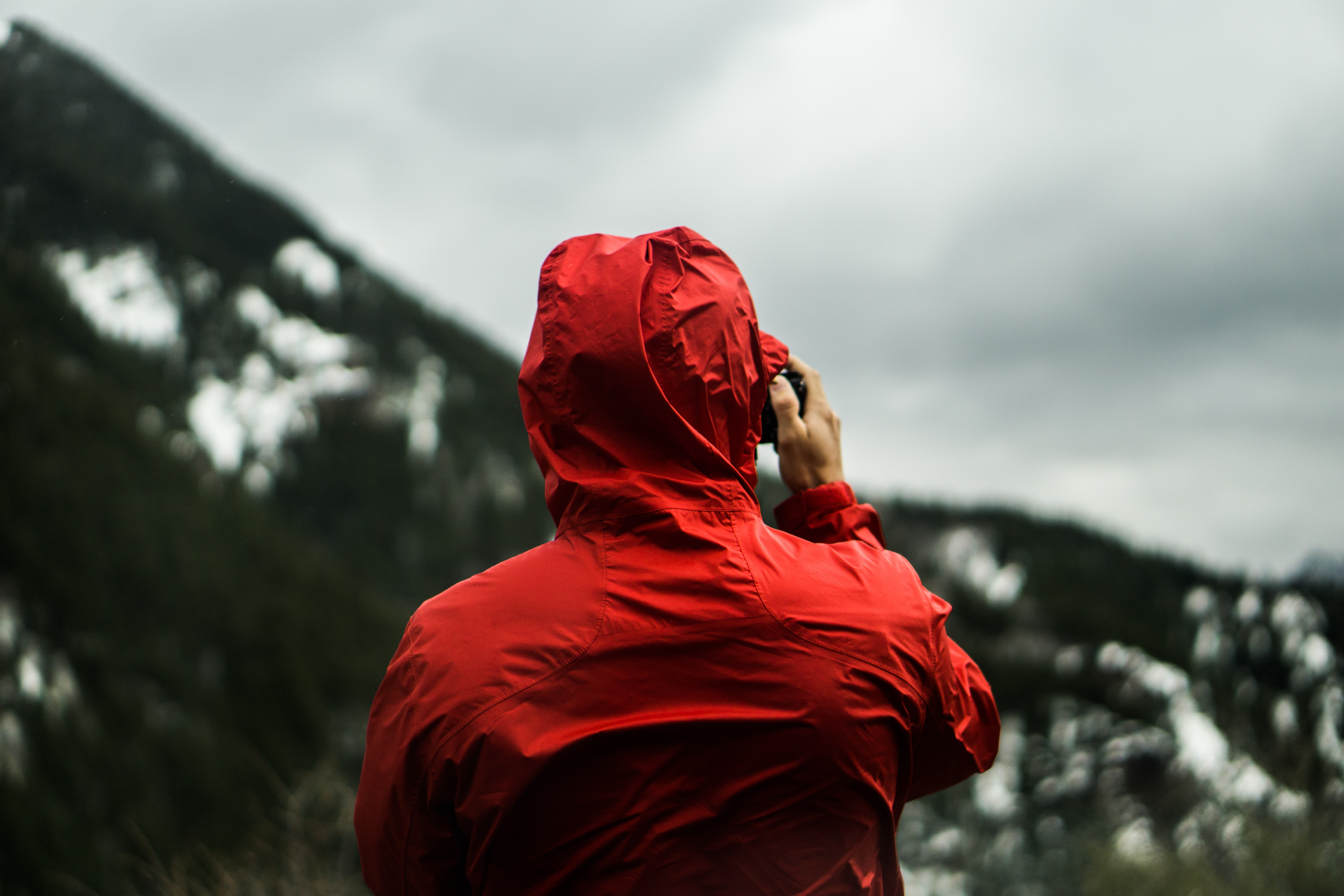 Person in a red jacket surveys a mountain landscape