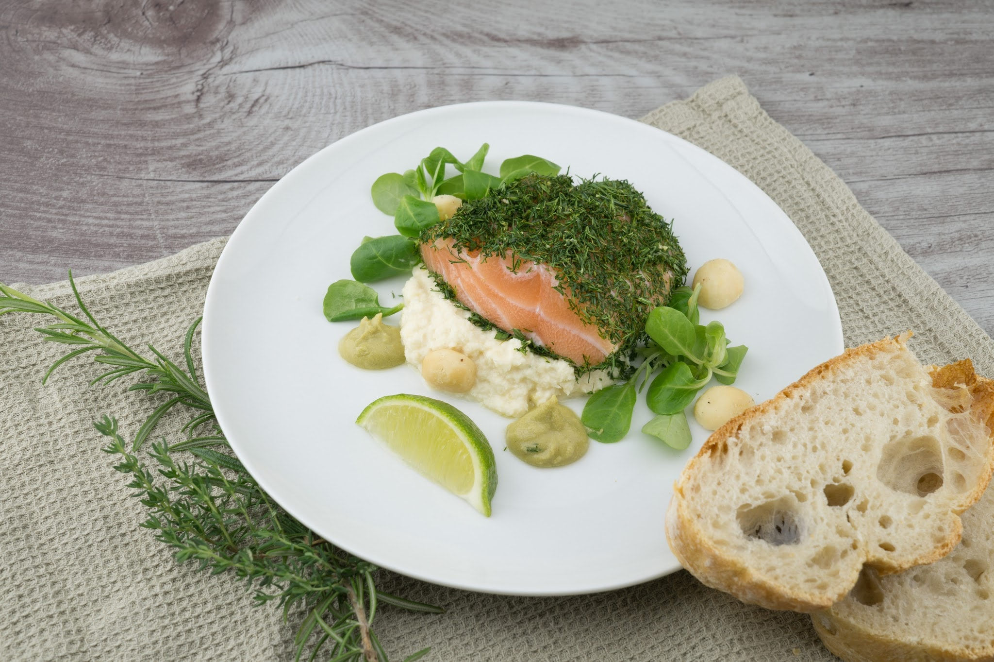 Plate with fresh salmon, lime, dill, and herbs and bread