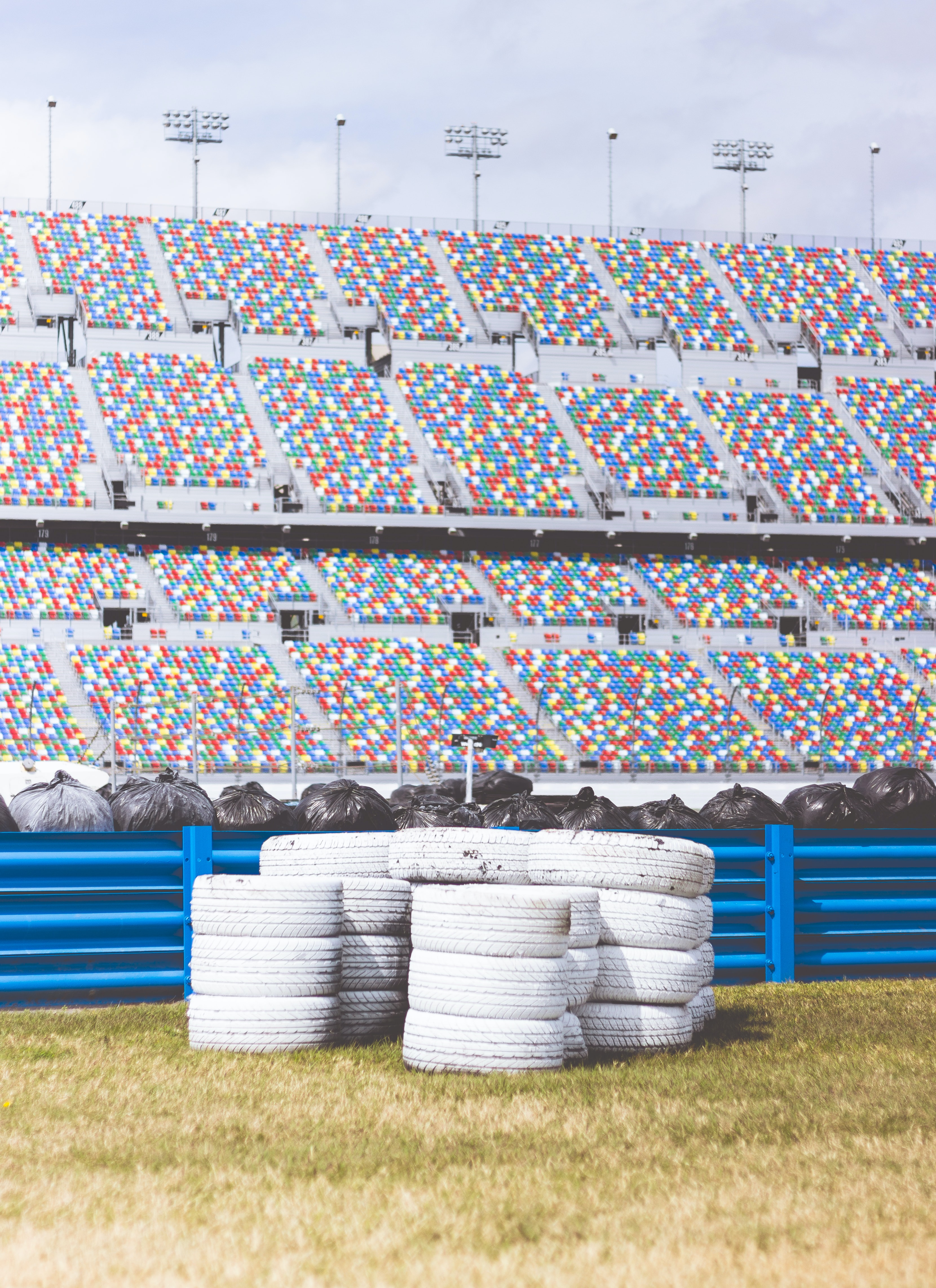 Stacks of white tires by the blue fence and large colorful stand at Daytona International Speedway