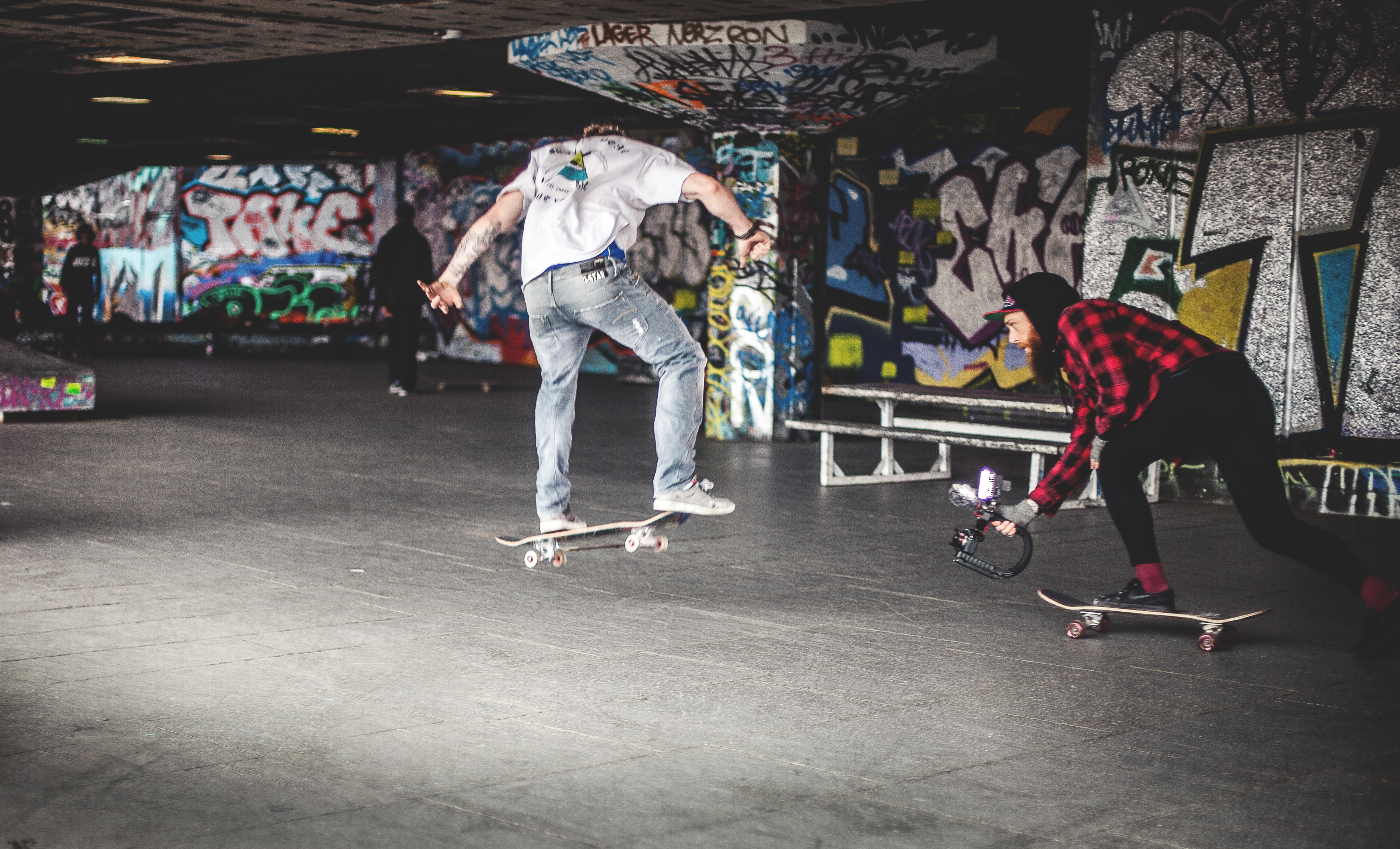Skateboarders do tricks inside a skate park with graffiti art
