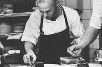 grayscale photography of chef preparing dish