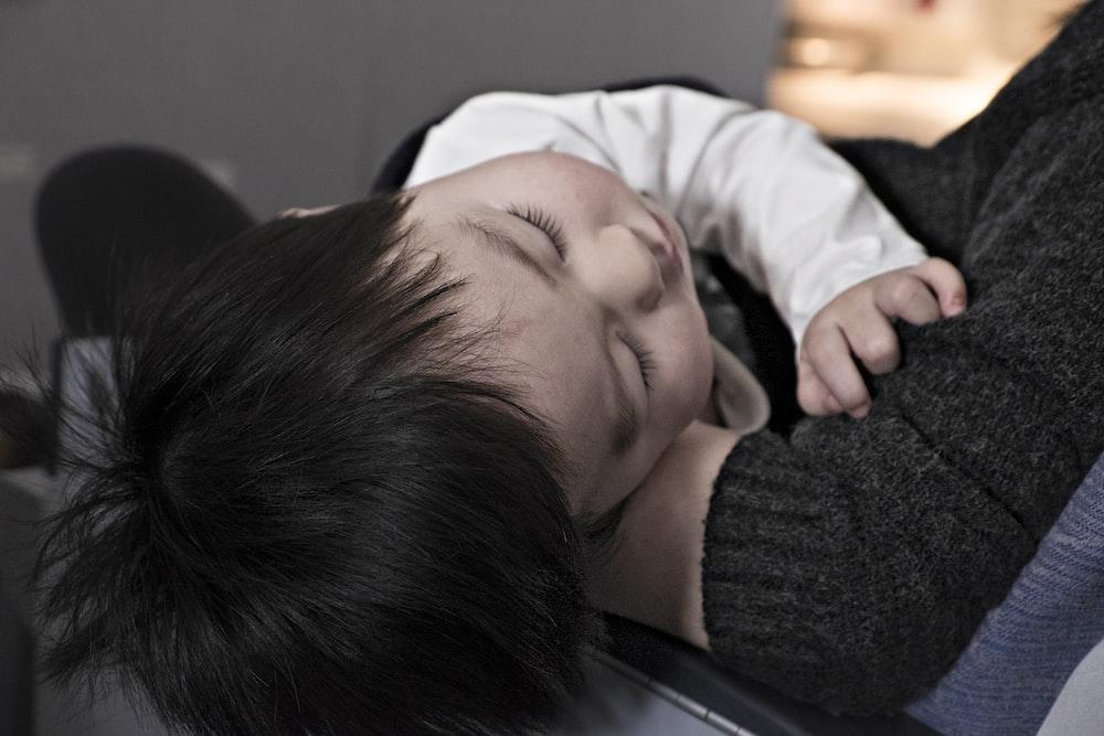 toddler sleeping on parent