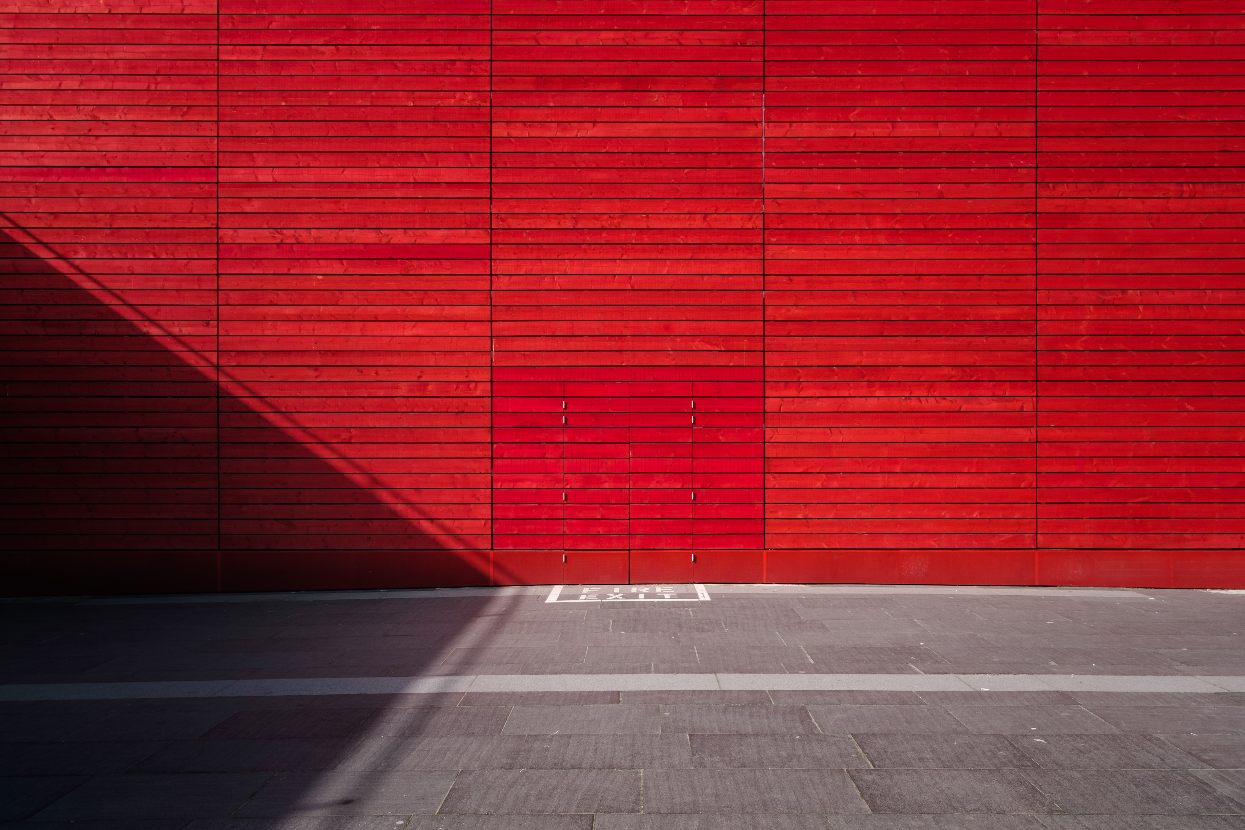 red painted wall and concrete pavement