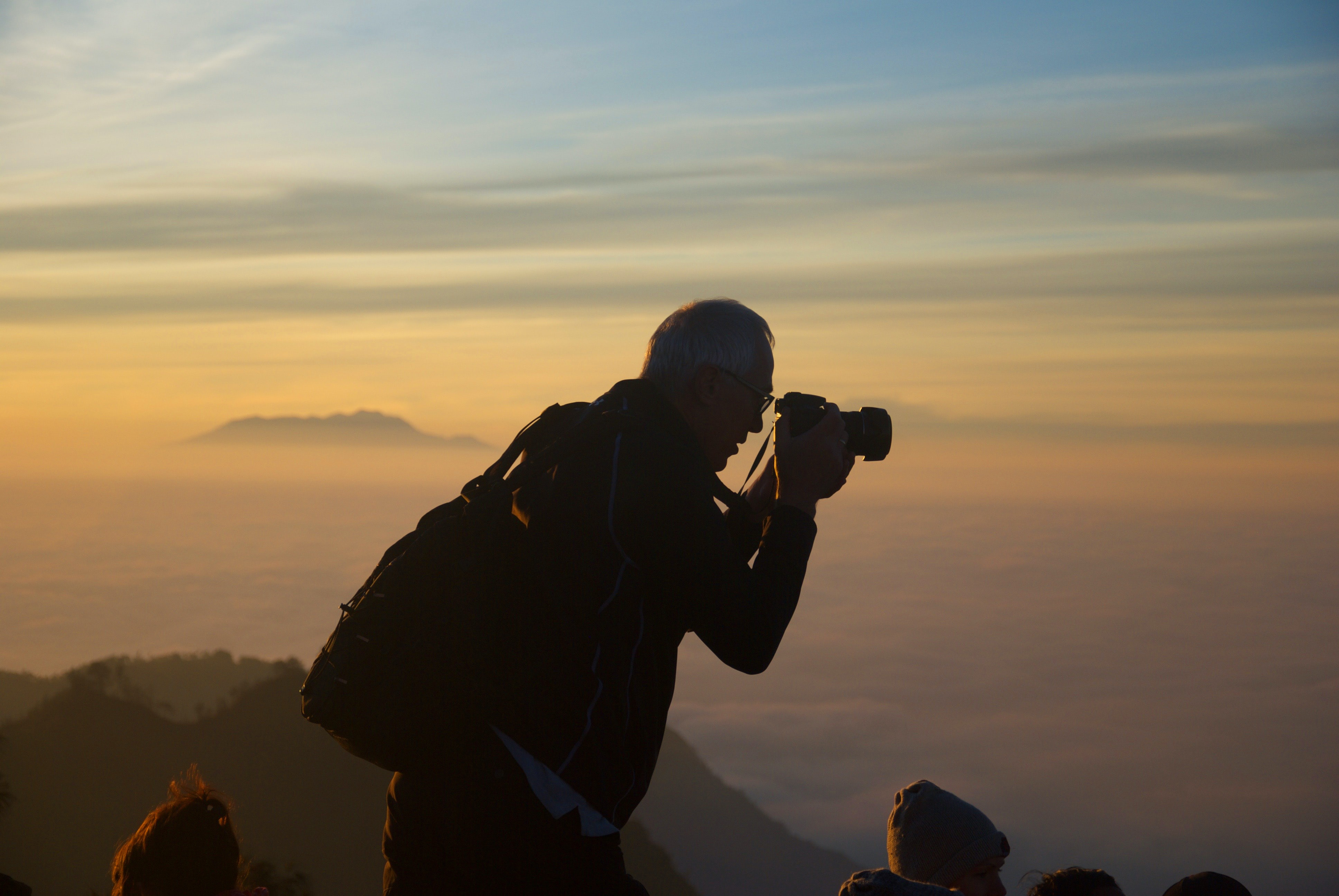 A silhouette of a man taking a photo while on top of a mountain