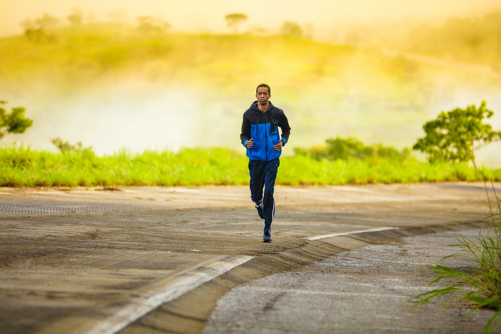 A male wearing a spring jacket, running along the side of the road in Brasilia