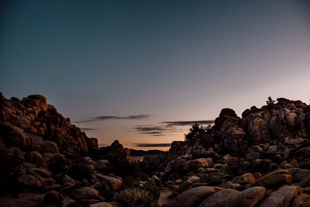 brown rocky shore during sunset