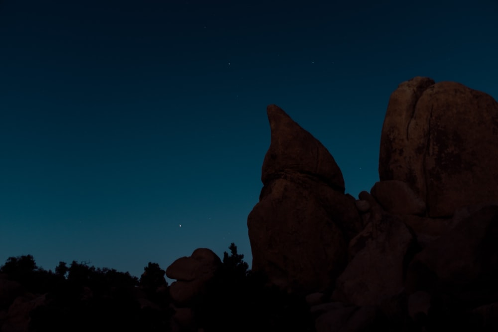 brown rock formation under blue sky during nighttime